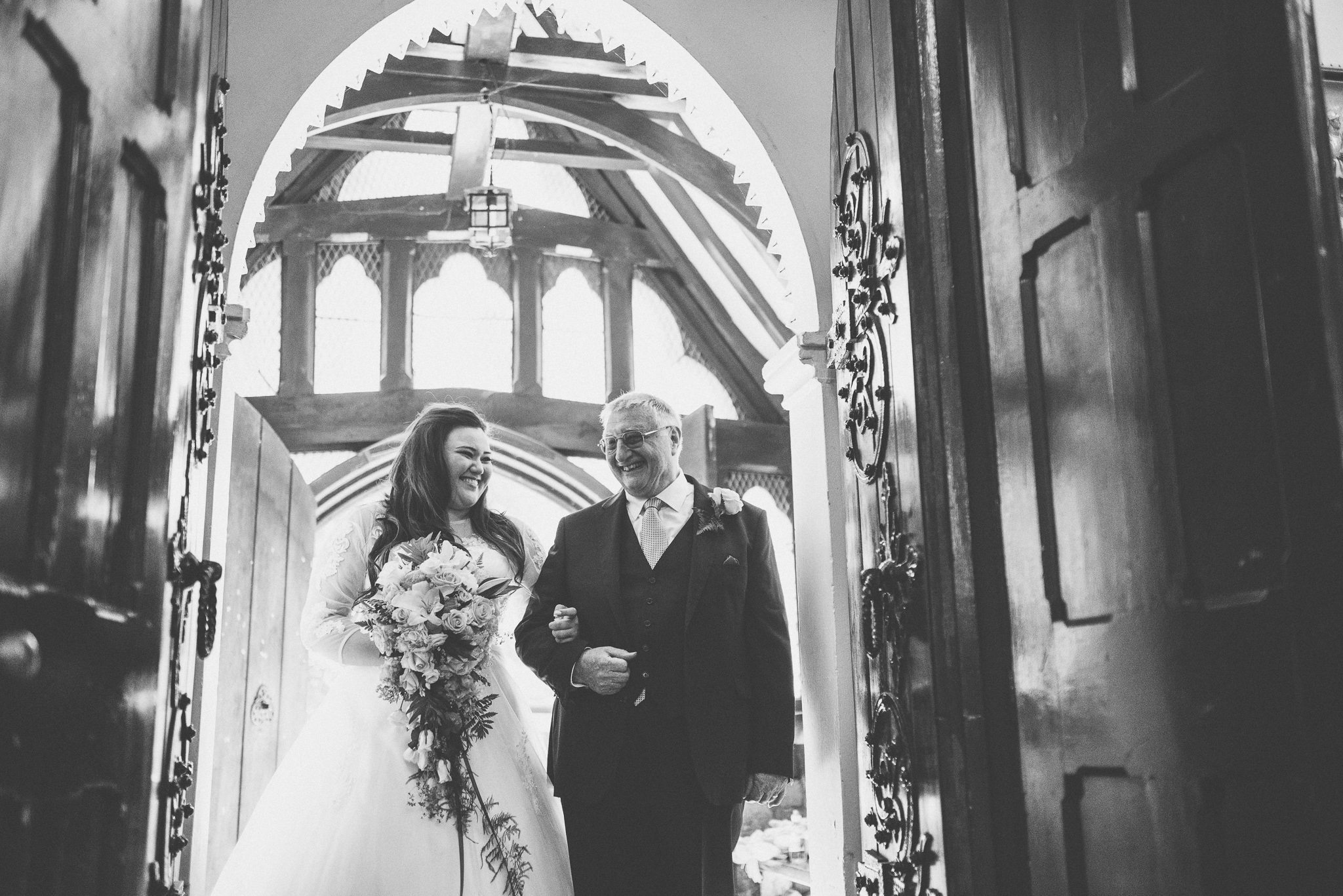 Bride and her dad smile at each other at the entrance to the church