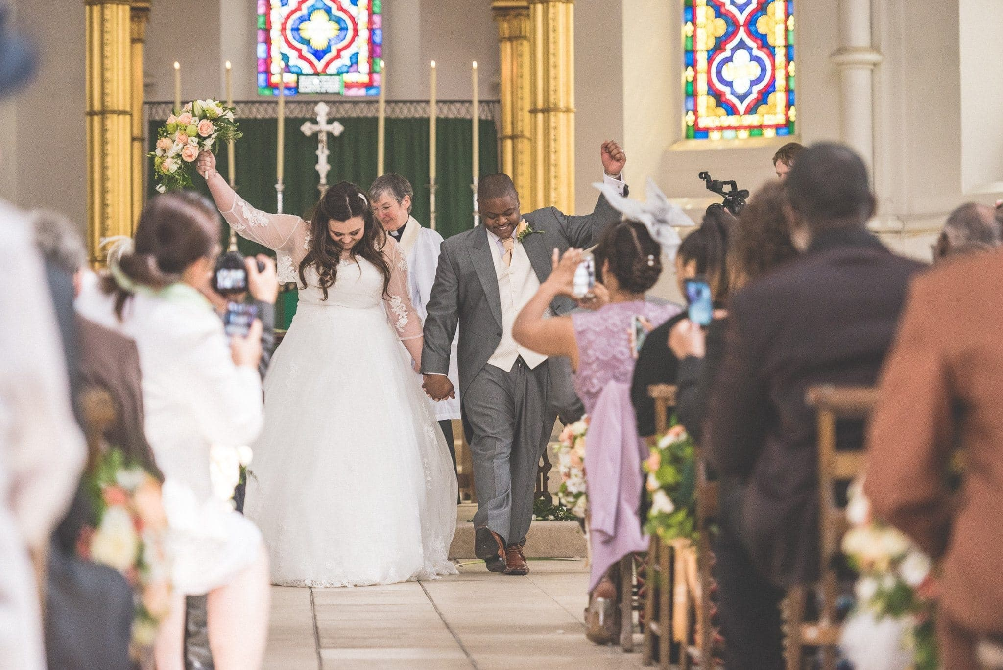 Bride and groom cheering as they walk down the aisle