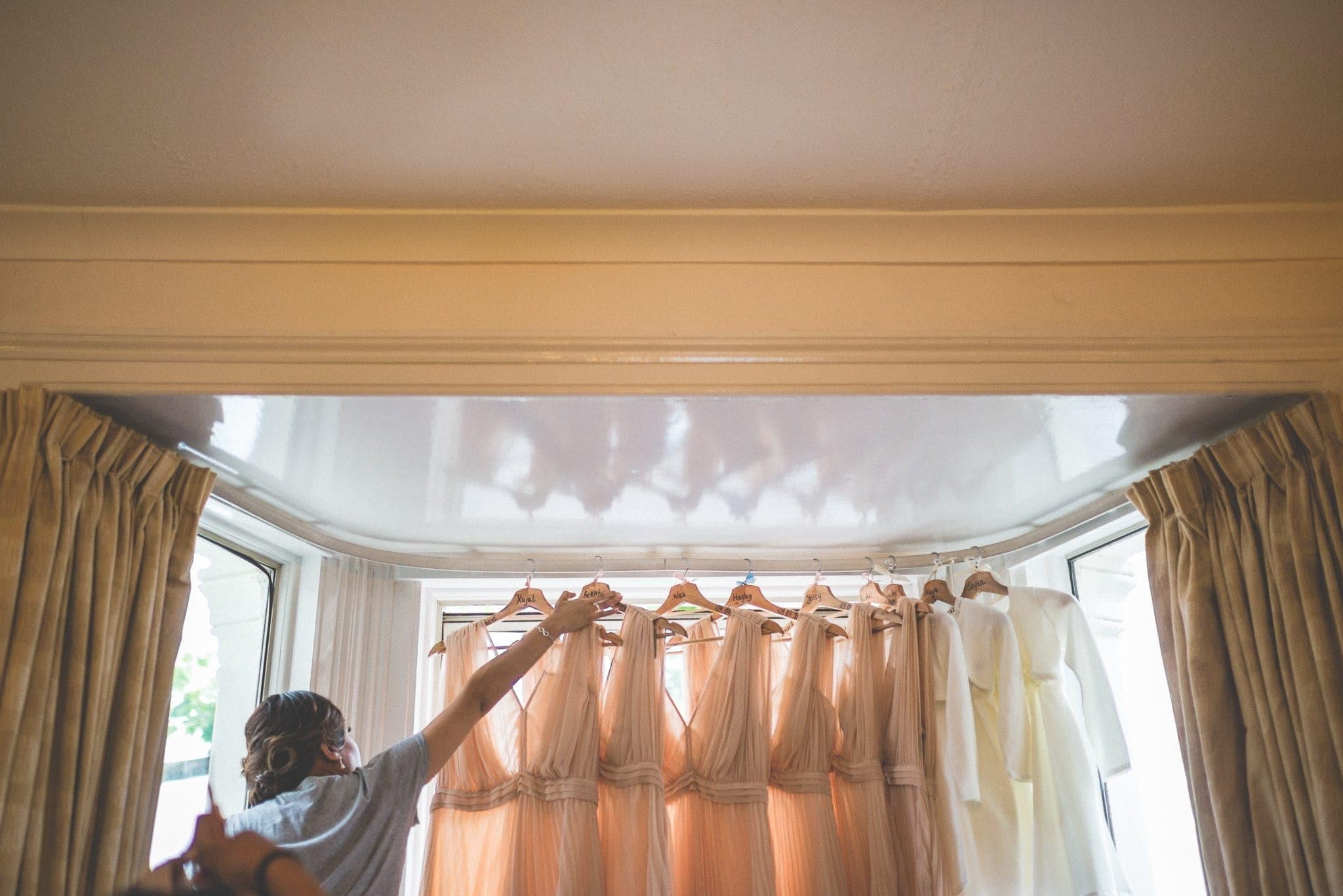 Bridesmaid taking down a bridesmaids dress from where they hang in the window