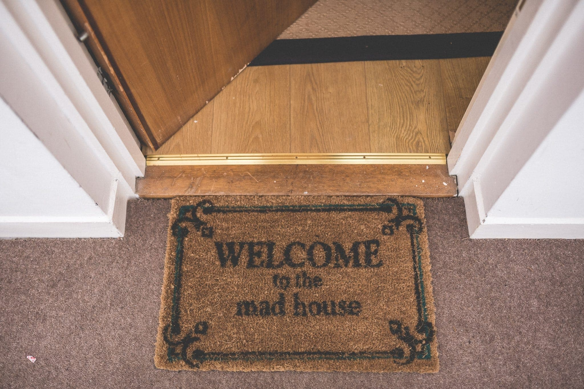 Door mat saying welcome to the mad house
