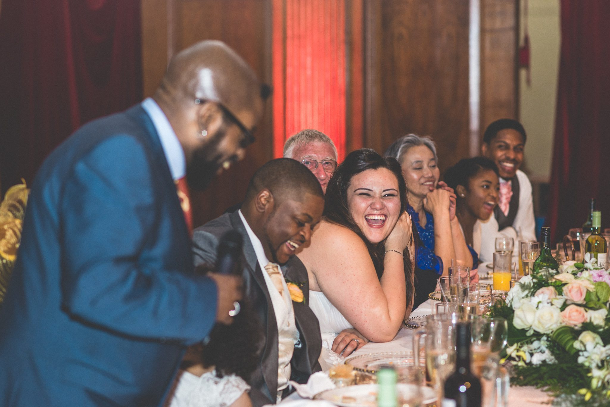 Bride and groom laugh at the Best Man's Speech at their Porchester Hall Wedding