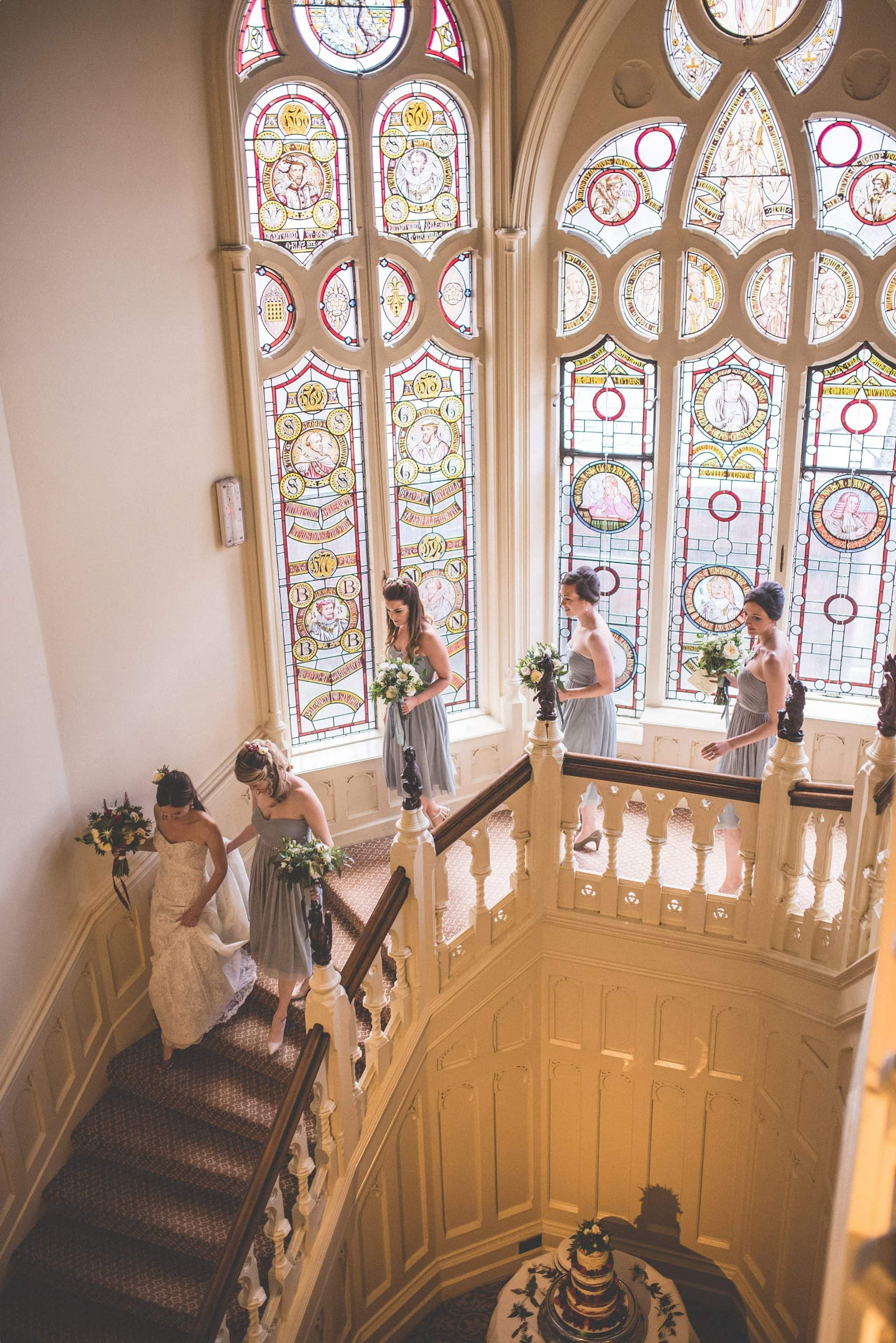 Bride and bridesmaids walking down the stairs at the elvetham hotel