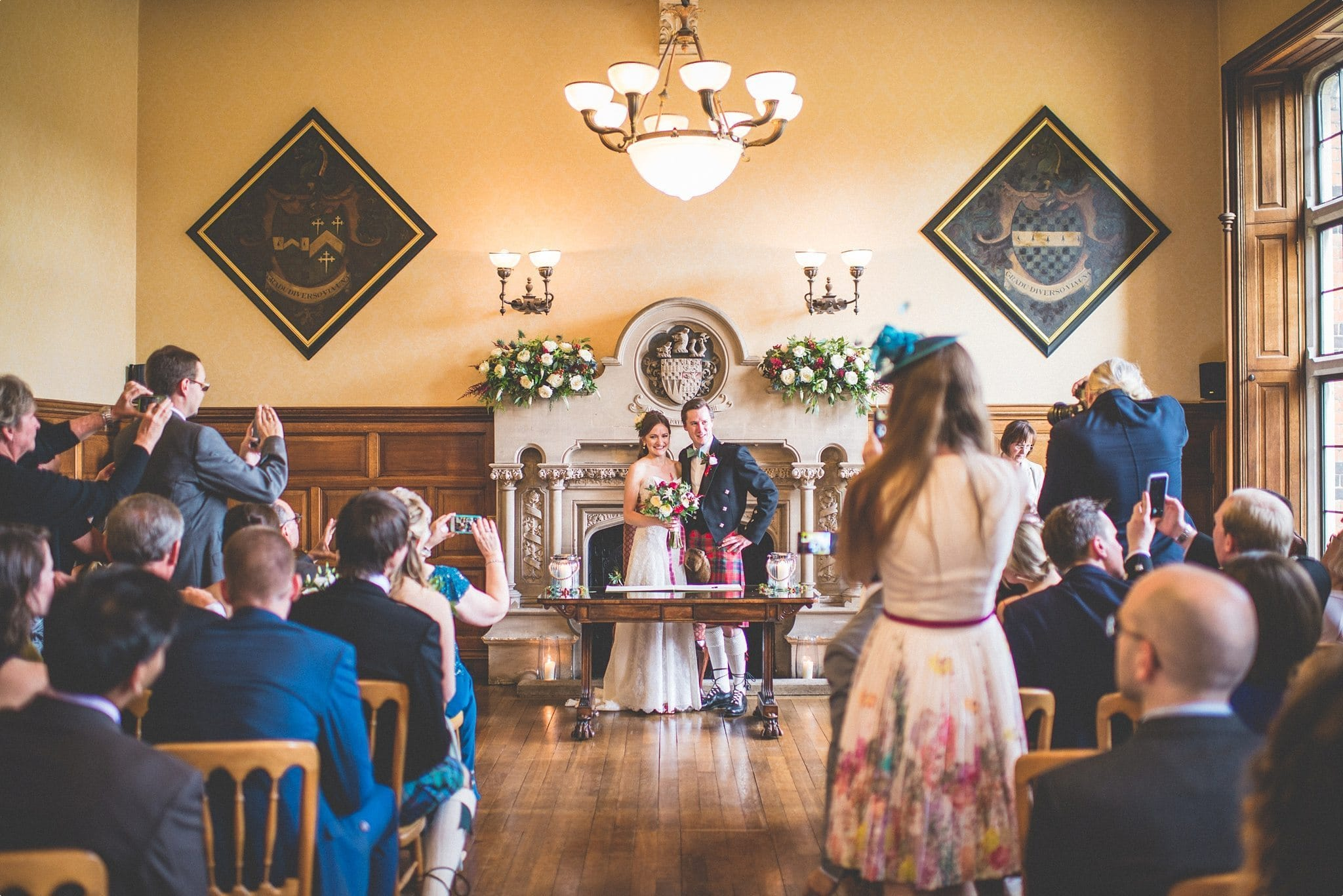Bride and groom smiling at their wedding ceremony guests at the Elvetham Hotel