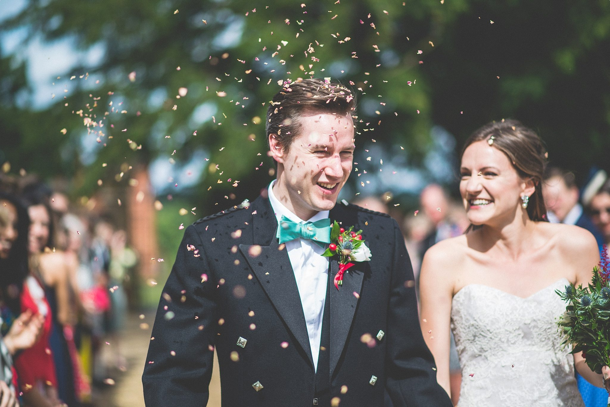 Bride and groom walking through confetti at the Elvetham hotel