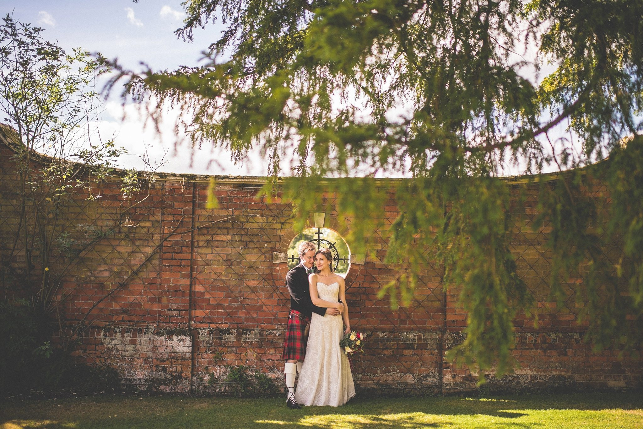 Bride and groom hugging at their Elvetham Hotel Kilts White Lace and Red Pumps Luxury Wedding
