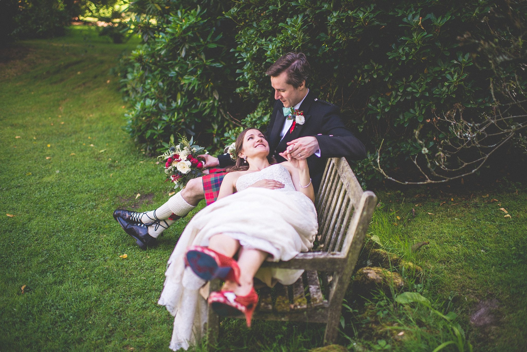 Bride and groom relaxing on a bench at the Elvetham Hotel