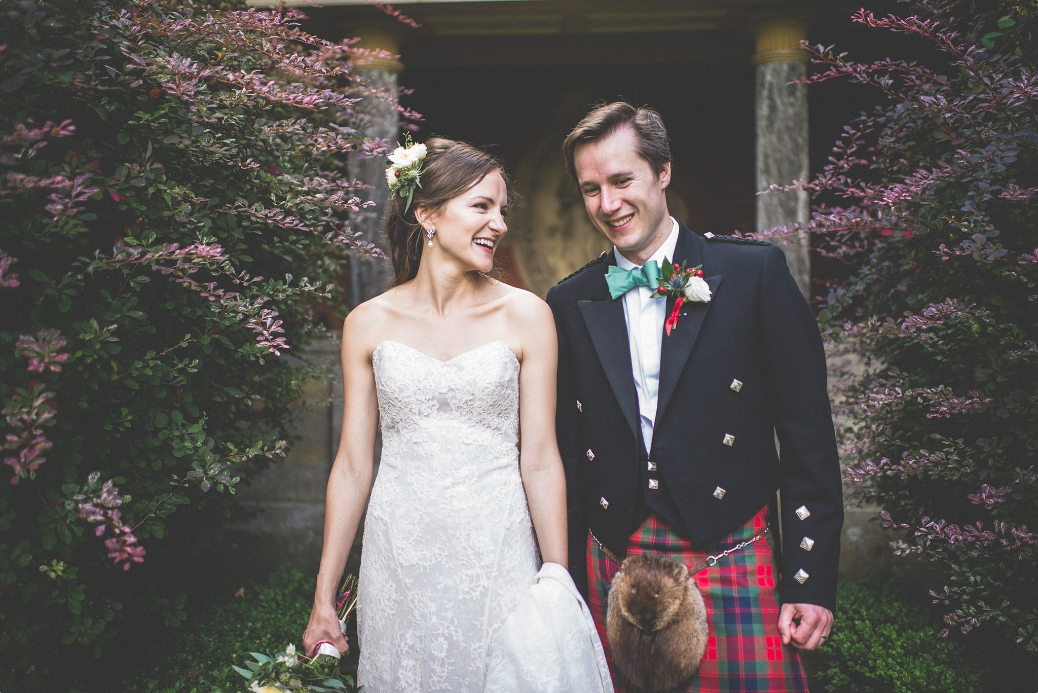 Bride and groom smiling at each other at their Elvetham Hotel Kilts White Lace and Red Pumps Luxury Wedding