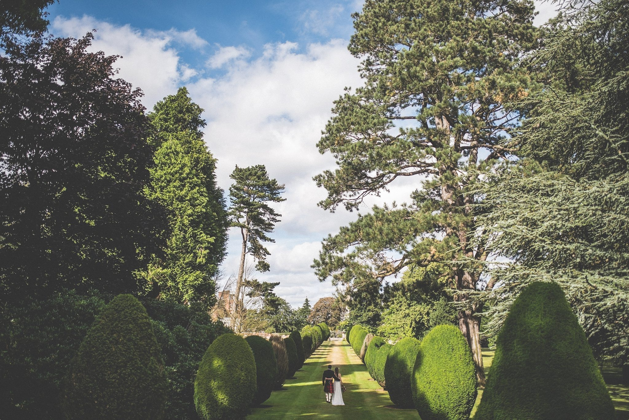 Bride and groom walking through the Elvetham Hotel grounds