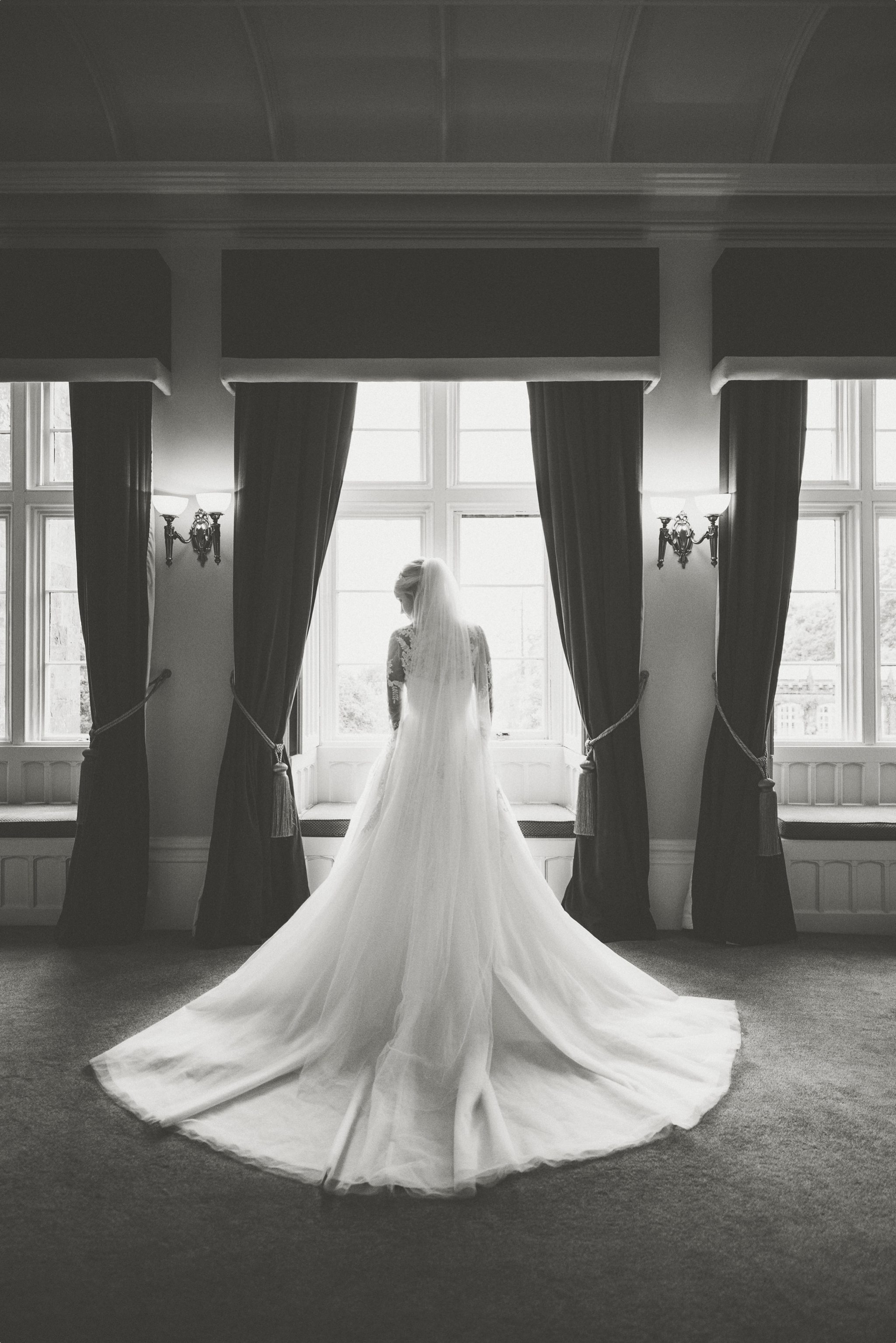 Bride standing in the window at her St Audries Park Sophisticated Rainy Wedding