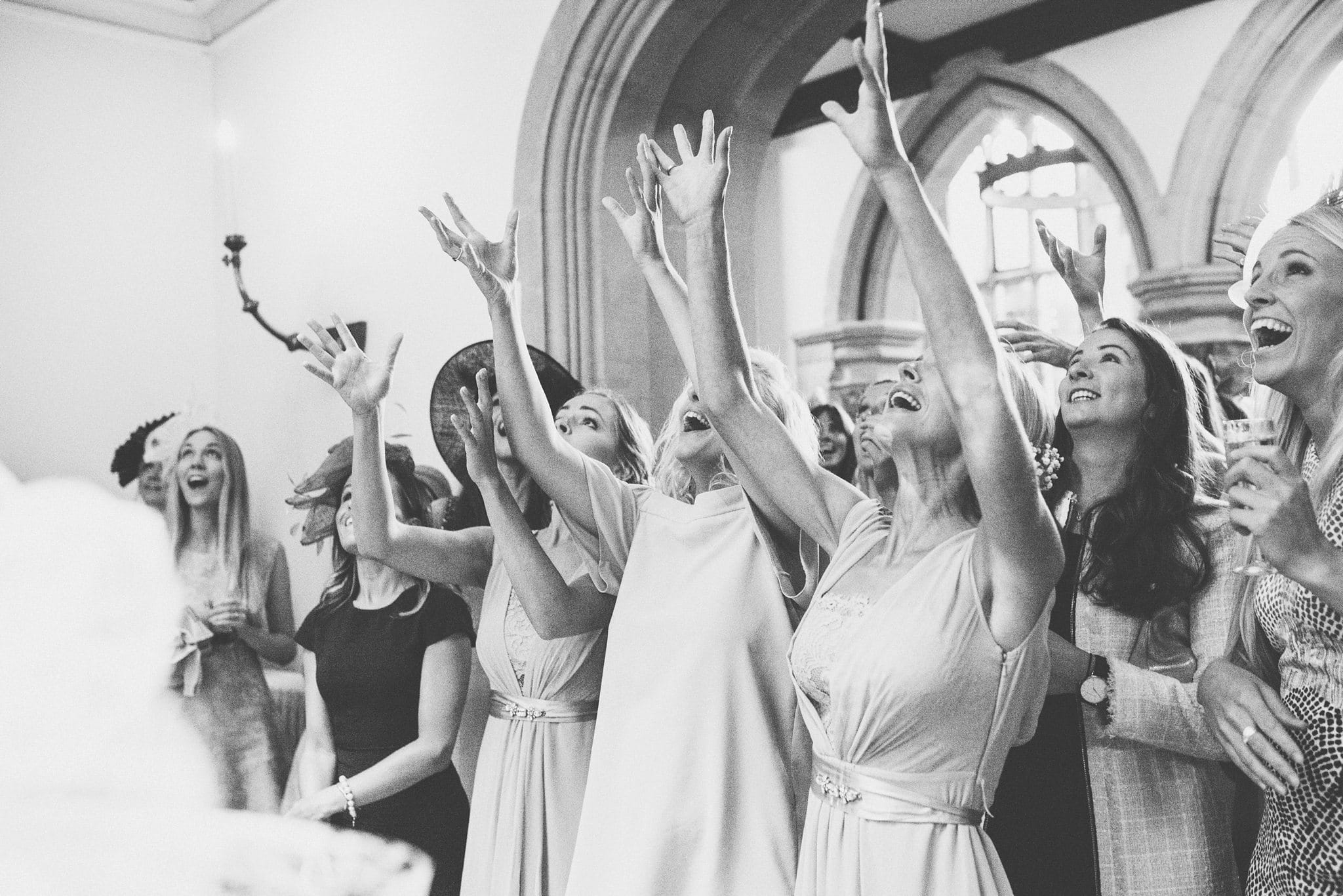 Girls jumping to catch the wedding bouquet at St Audries Park