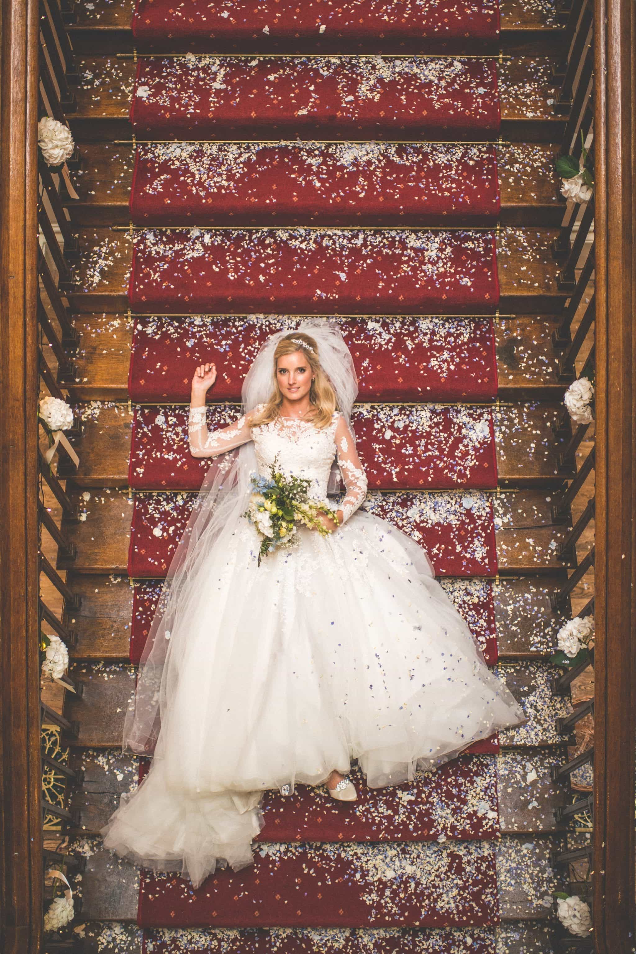 Bride lying on the stairs at her St Audries Park sophisticated rainy wedding