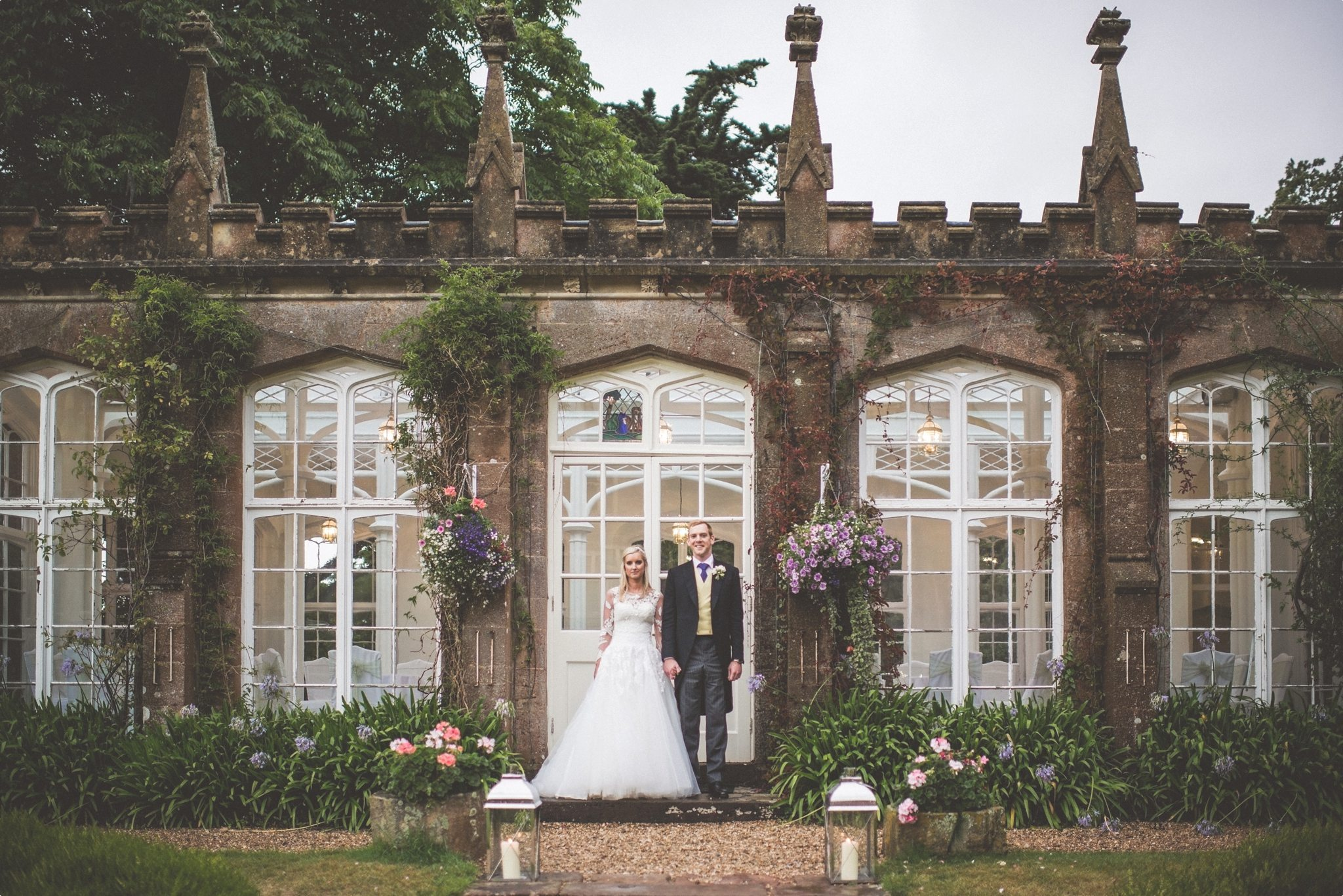 Bride and Groom standing at the glass conservatory at St Audries Park
