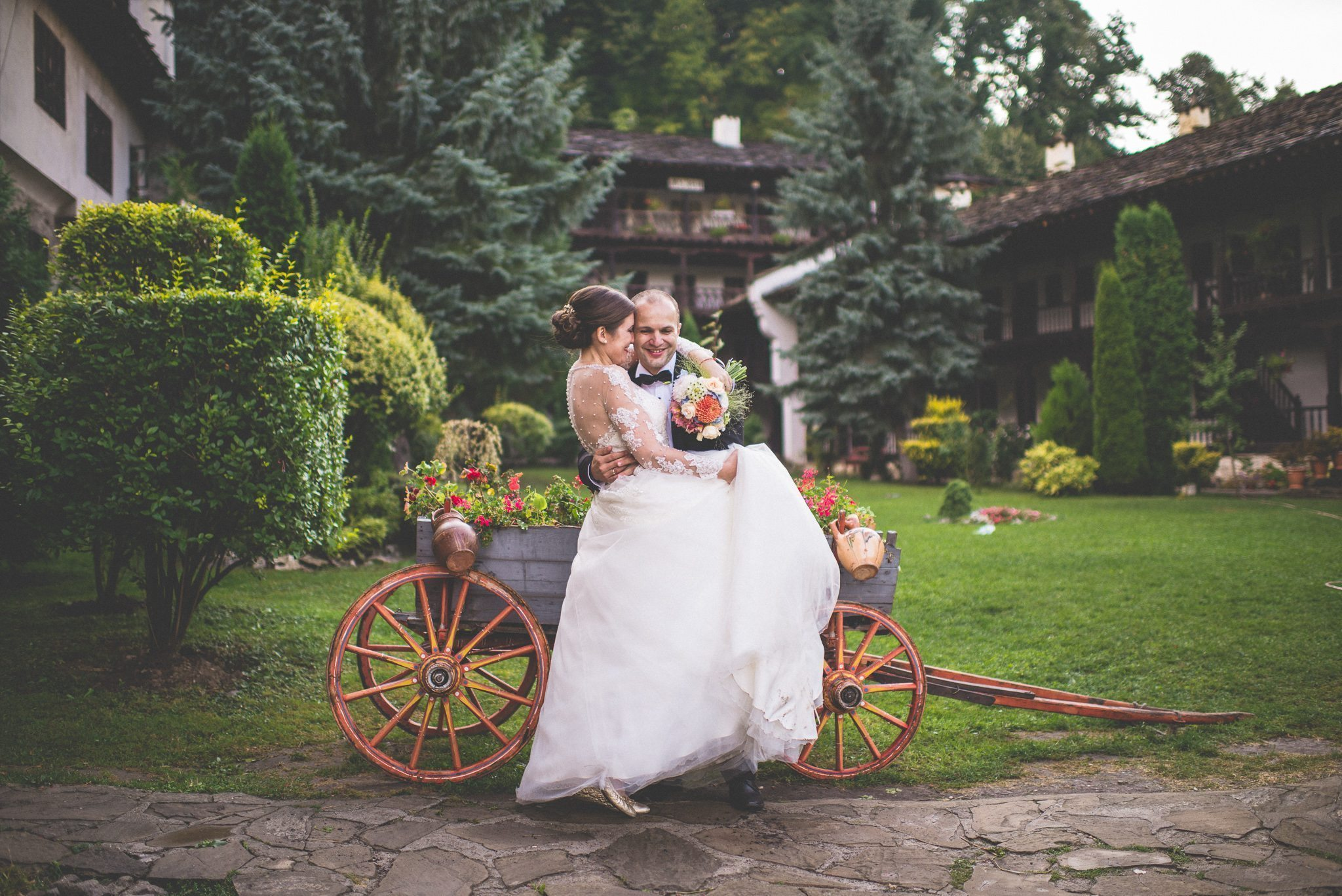 A bride kisses her groom on the cheek. They sit in a flower filled carriage in the grounds of a monastery