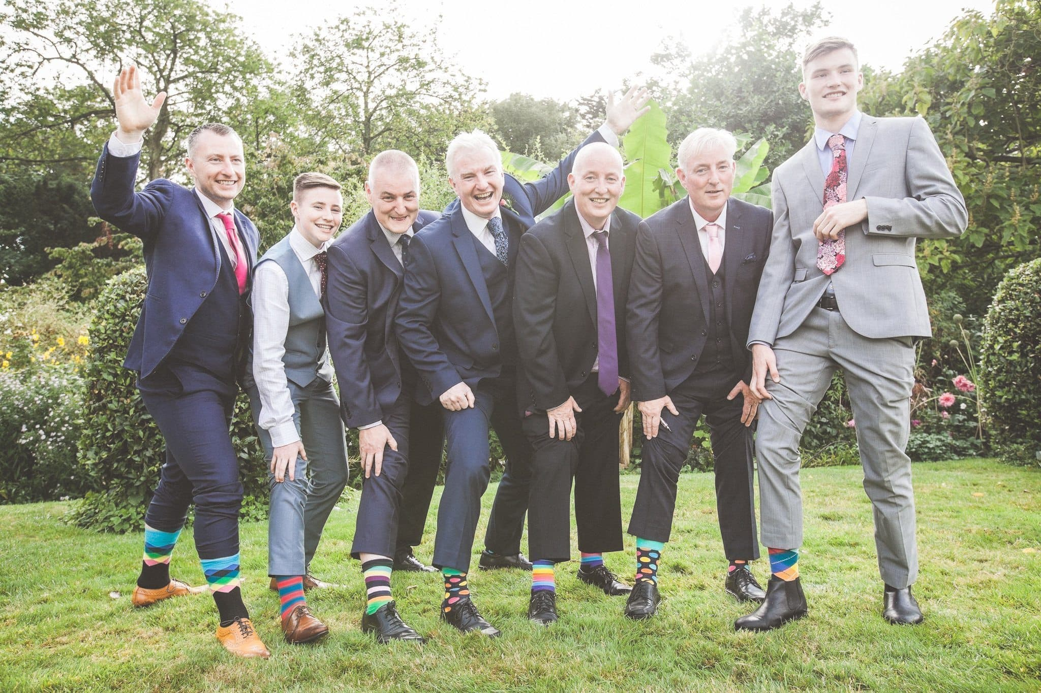 The groomsmen show off their colourful socks