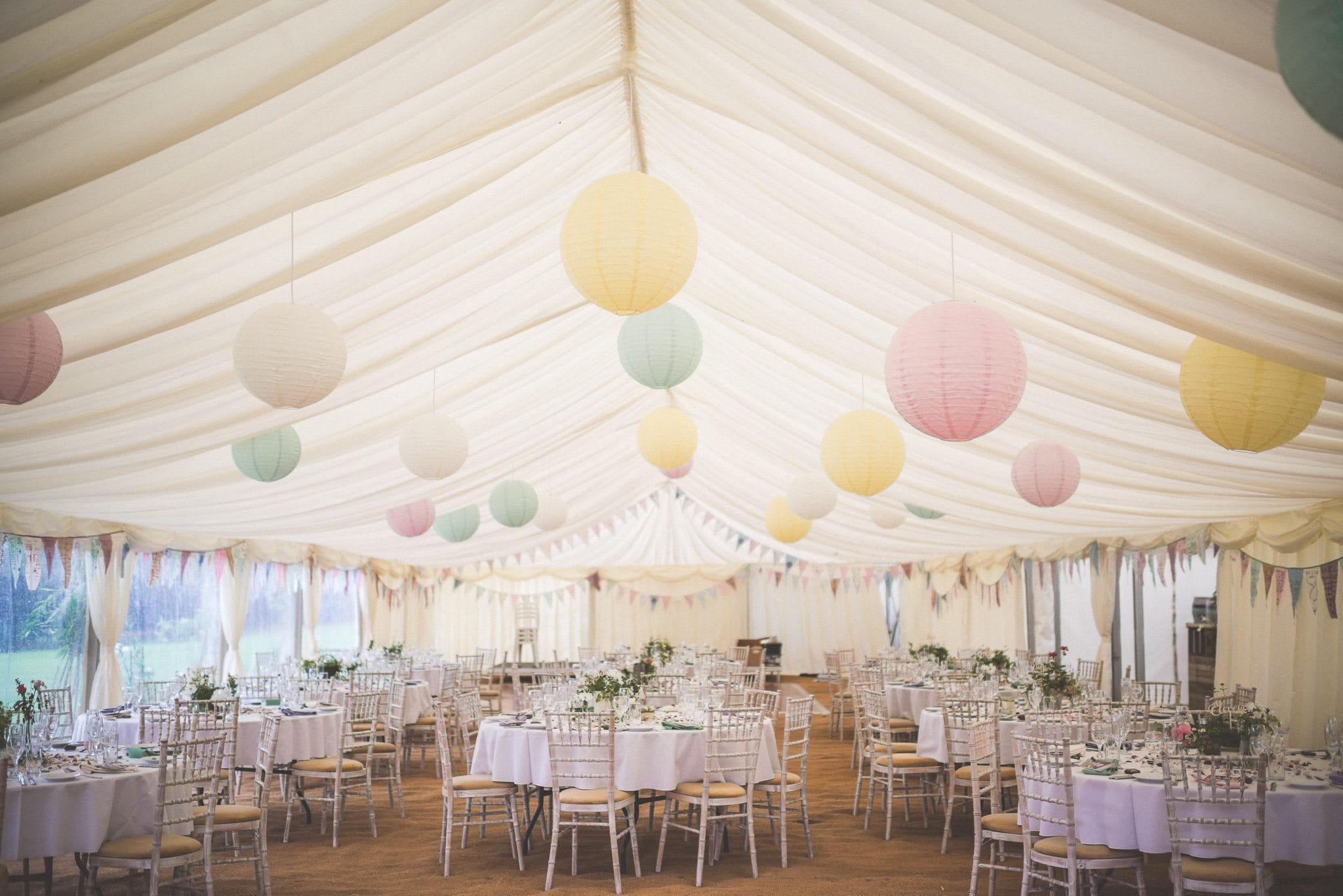 Marquee for reception decorated with hanging lanterns in pastel hues