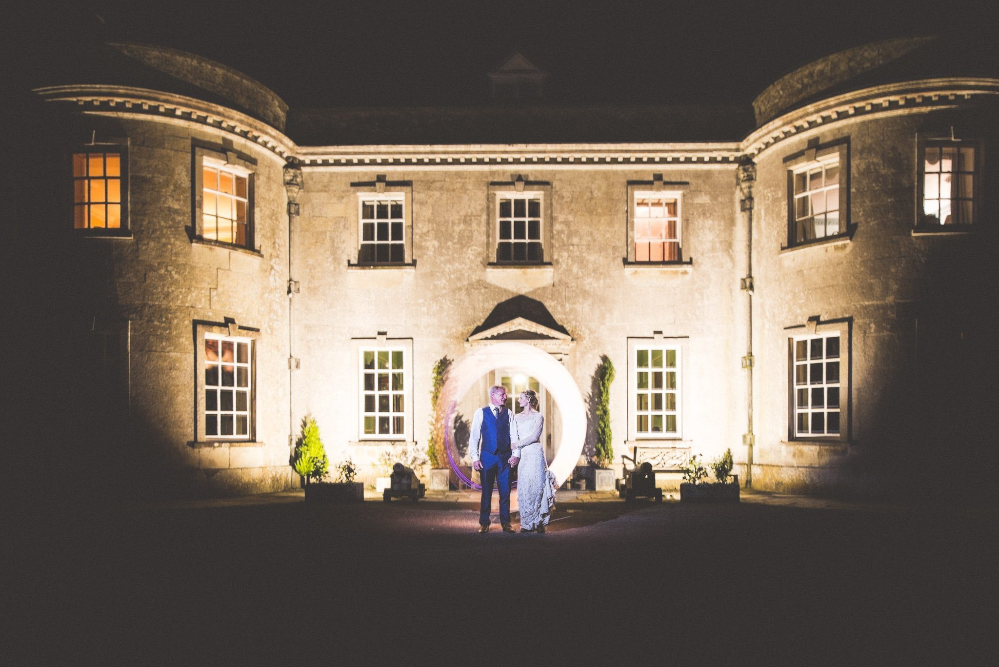 Bride and groom stand outside Smedmore House at night, lit by a circle made of sparklers