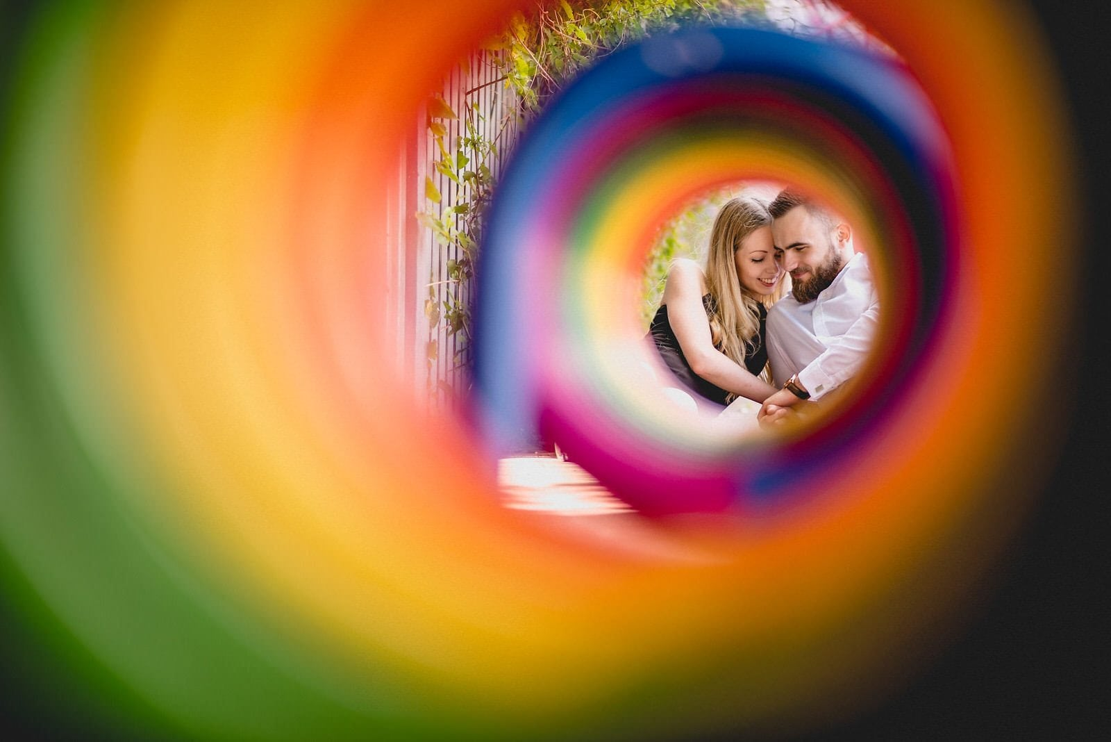 Bride and groom snuggle and smile seen through colourful rainbow circles