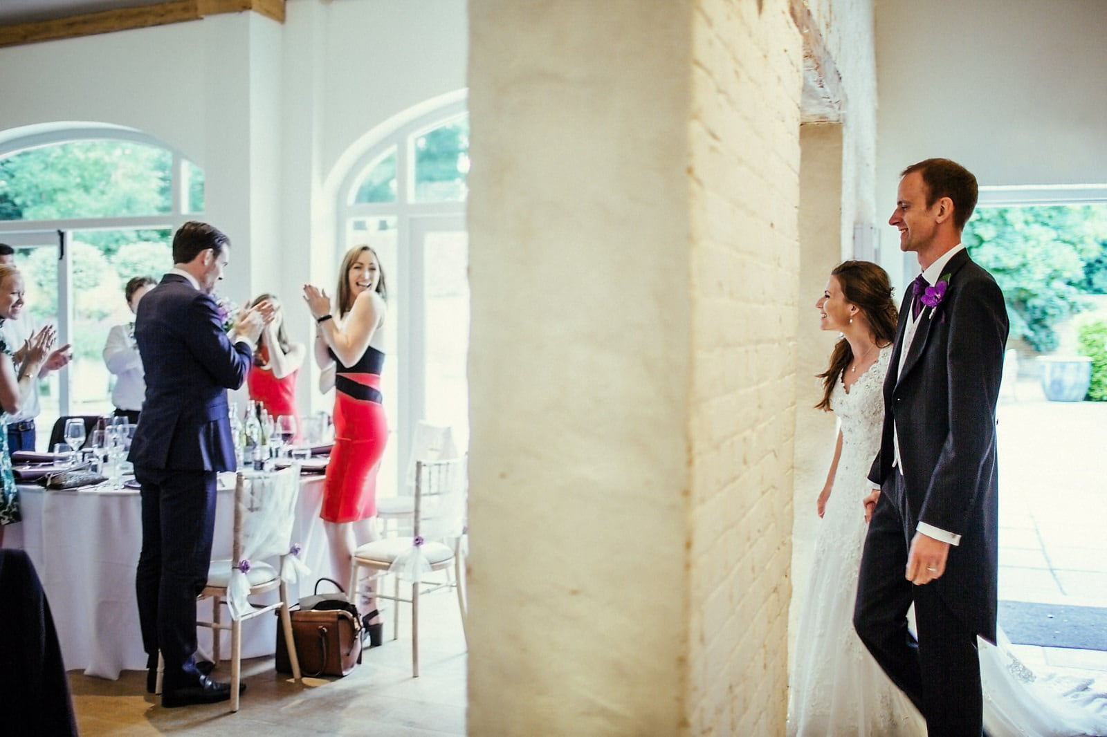 Bride and groom walking into their wedding reception with their guests cheering at Dorney Court