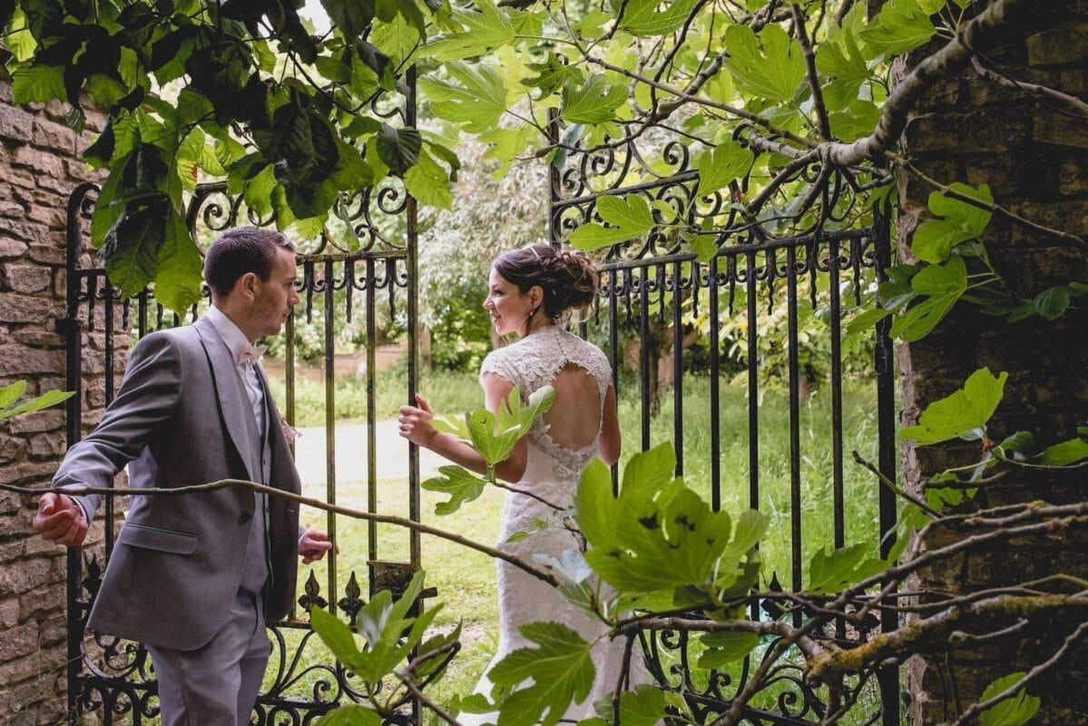 Bride and groom entering a secret garden gate