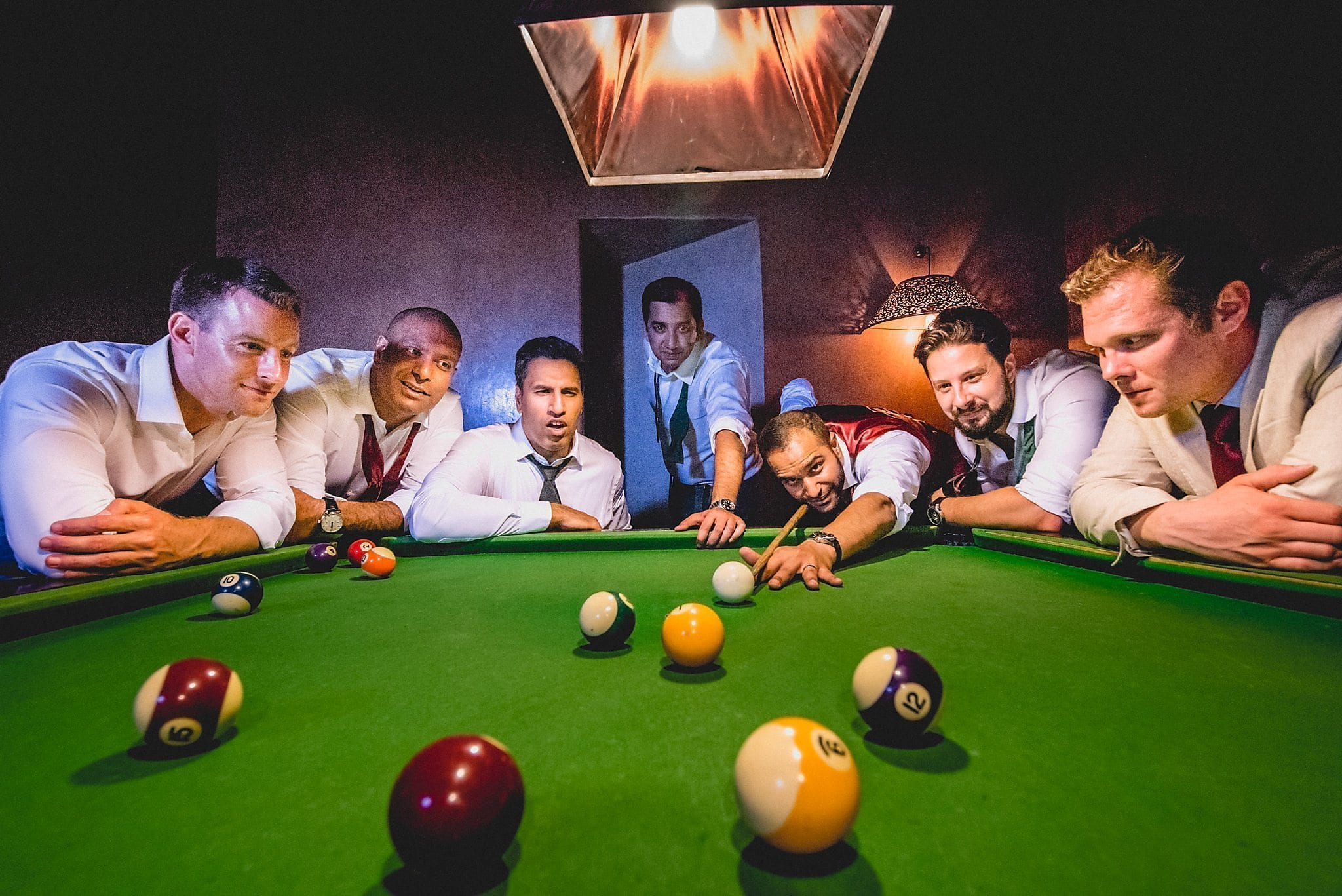 Groom and groomsmen play pool at their destination wedding at Morocco's Ksar Char Bagh