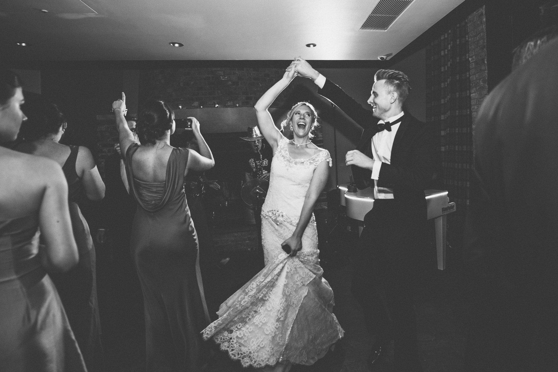 Bride in a lace fishtail dress being spun around on the dance floor