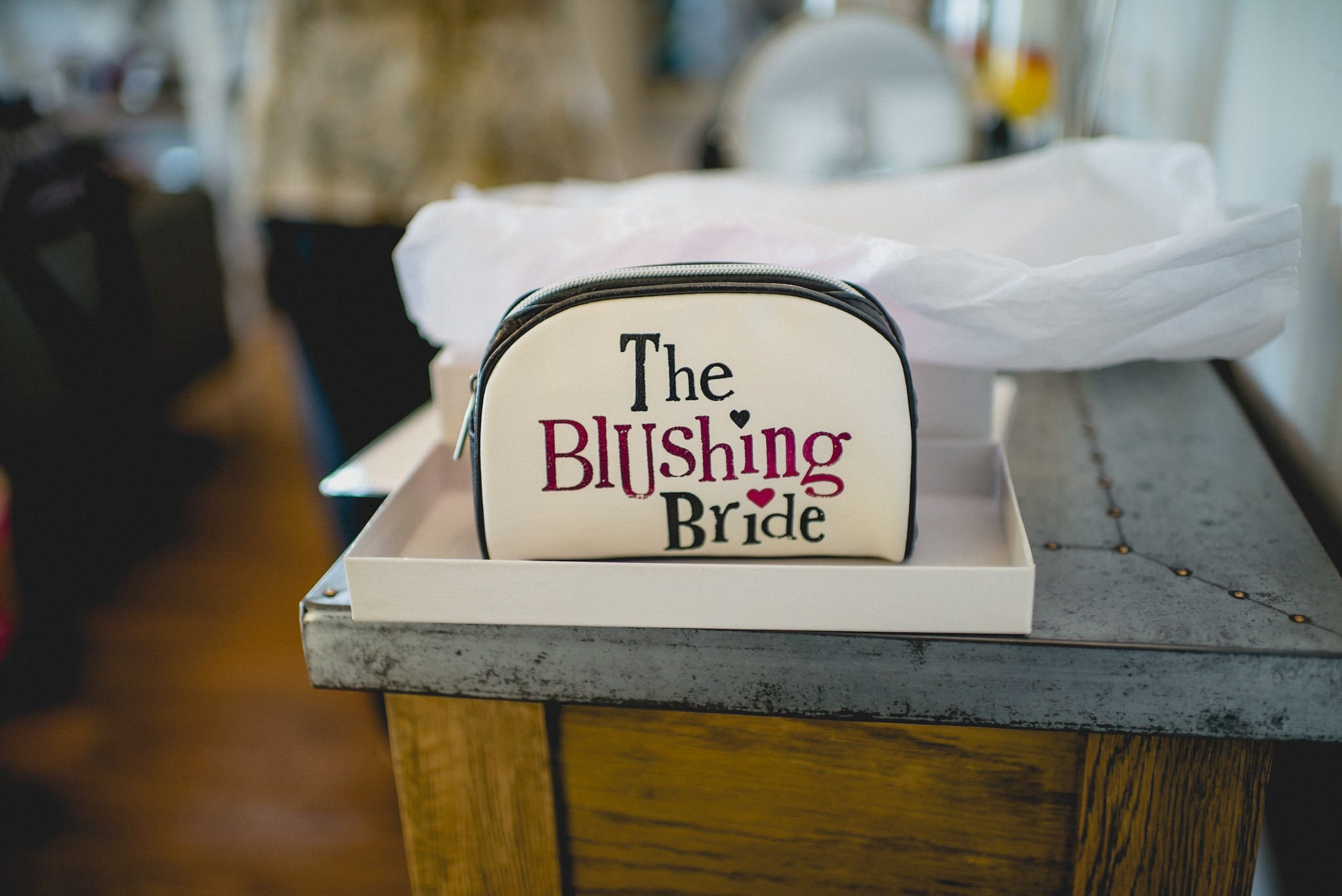A cream a black leather make-up bag with the words 'The Blushing Bride' on the side.