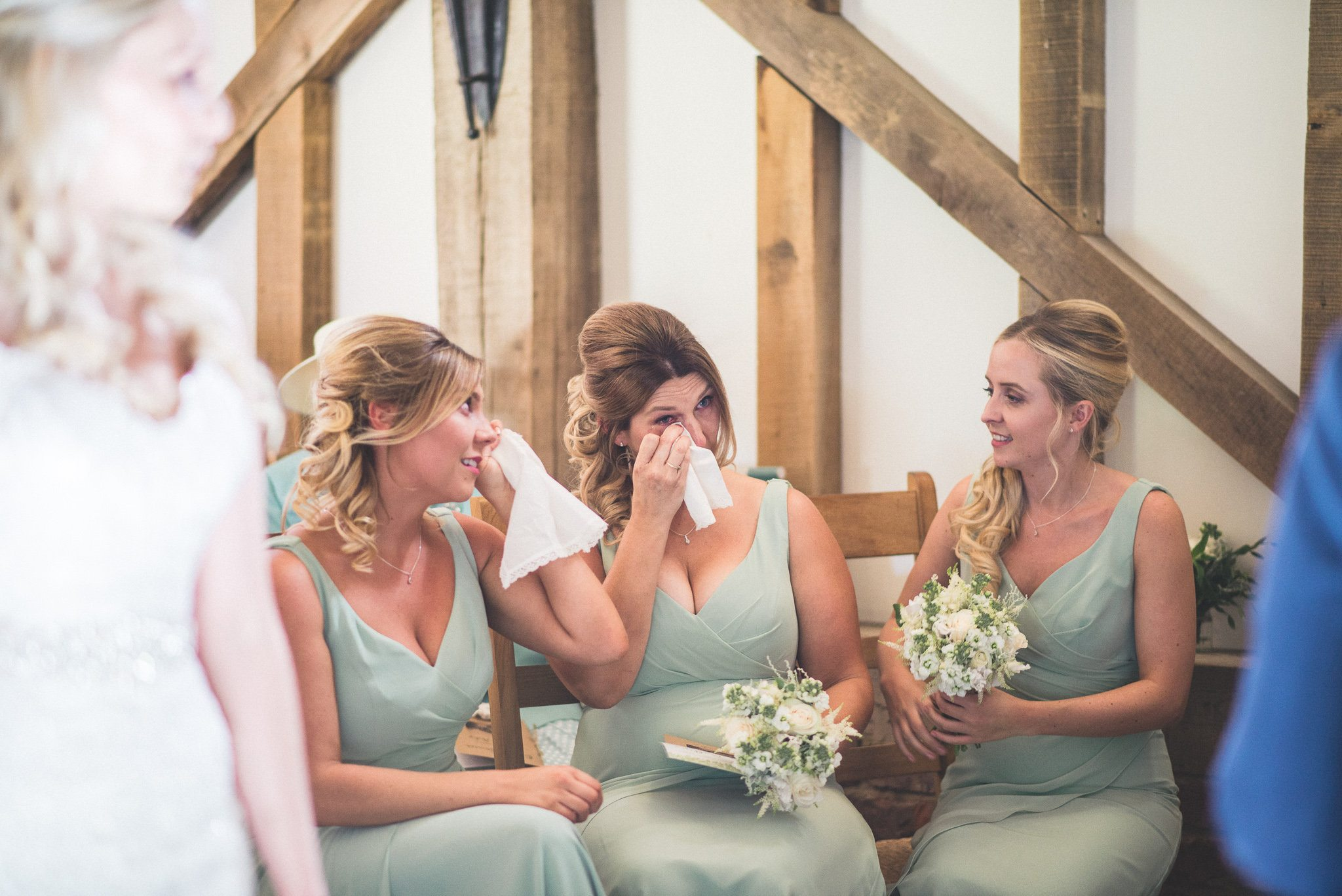 Three bridesmaids in mint green dresses wipe their eyes at a barn wedding