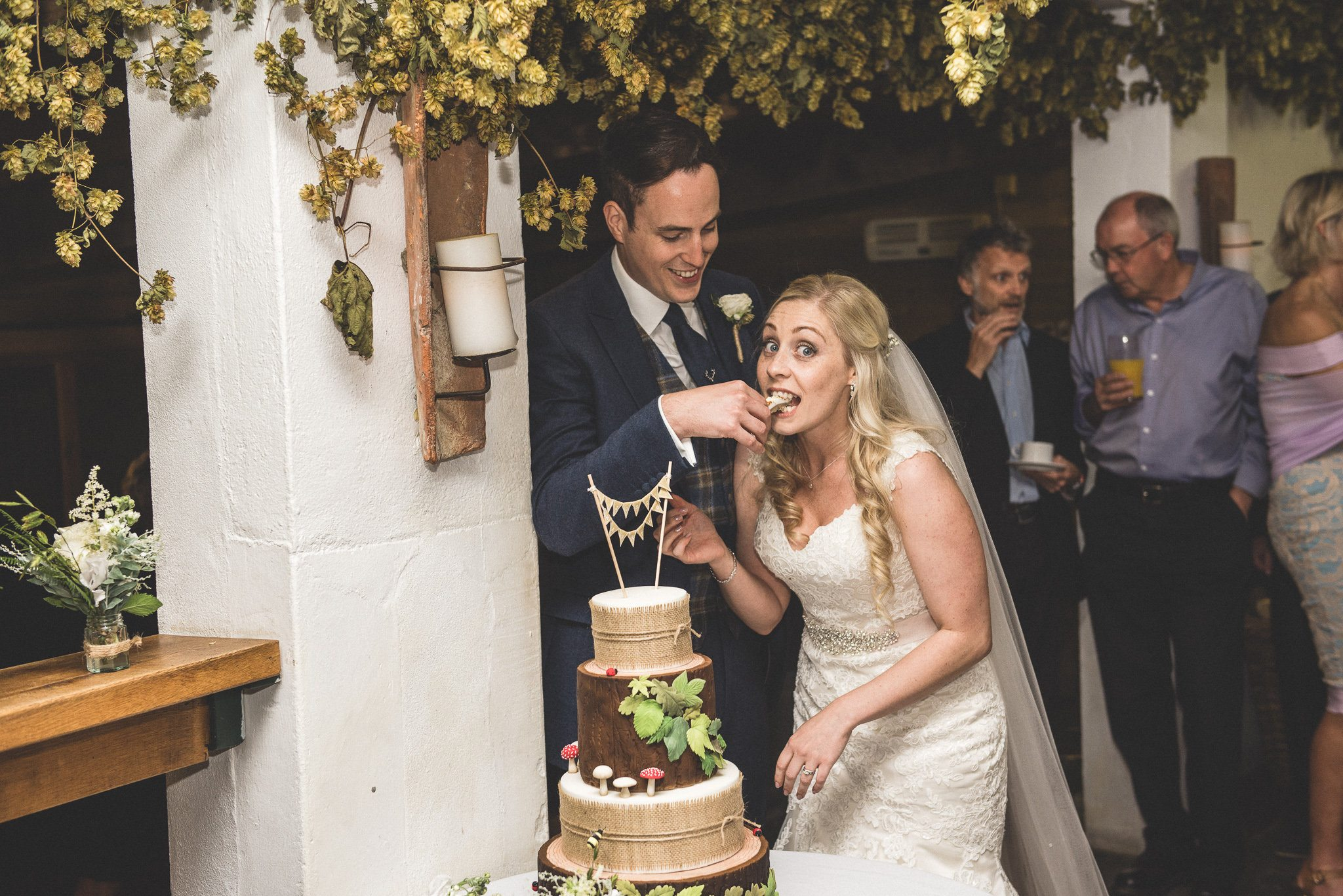Bride Emma is caught looking sheepish with a mouthful of wedding cake fed to her by her groom