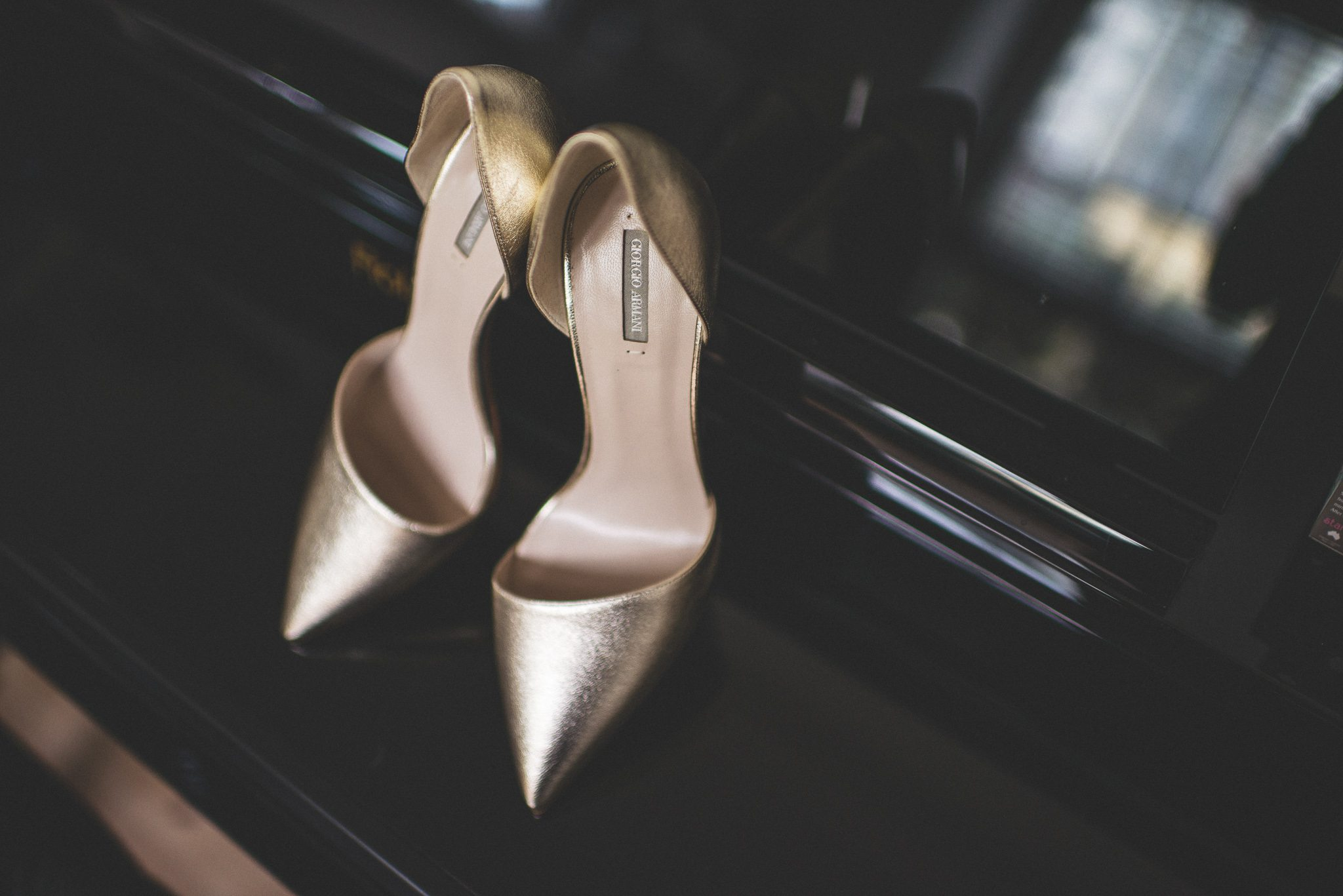 A pair of gold Armani stilettos are draped over a black piano