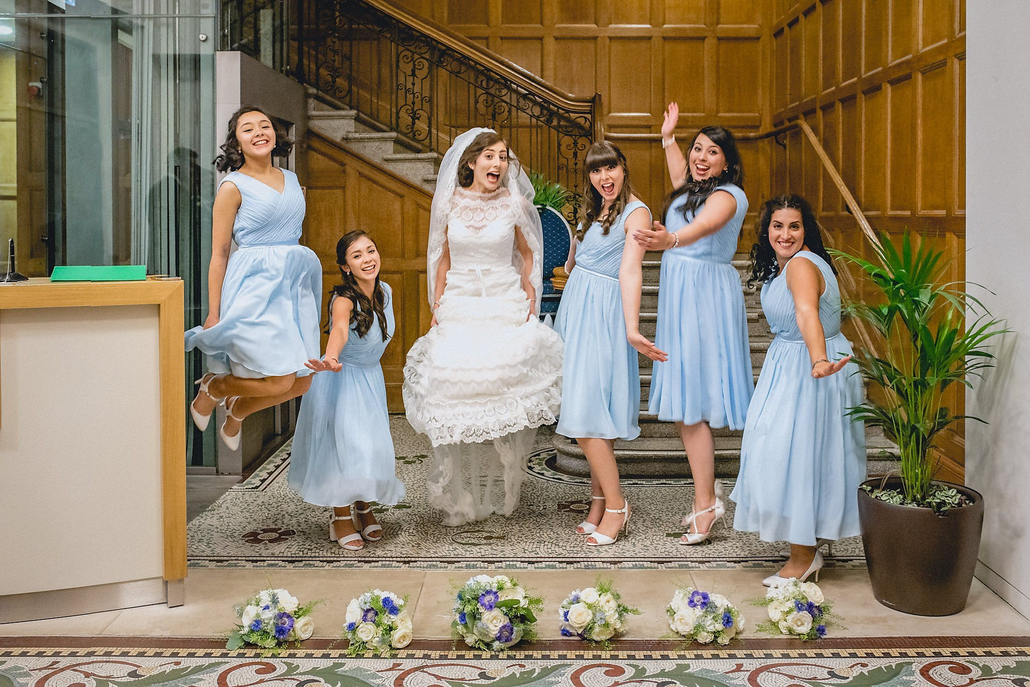 Bride Maria jumps in the air with her 5 bridesmaids, who are wearing pale blue dresses