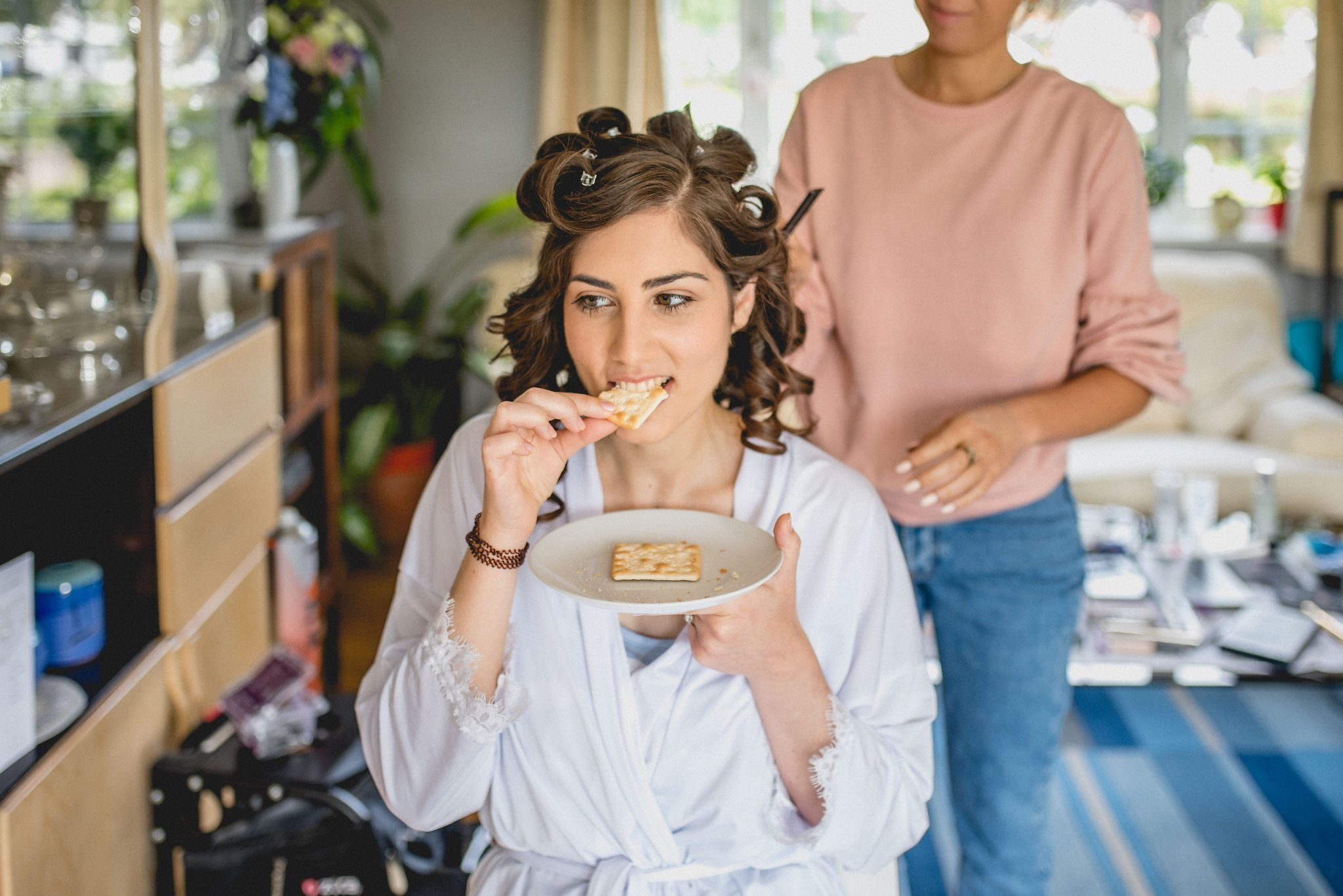Bride Maria snacks on some crackers while getting her hair done before her wedding.