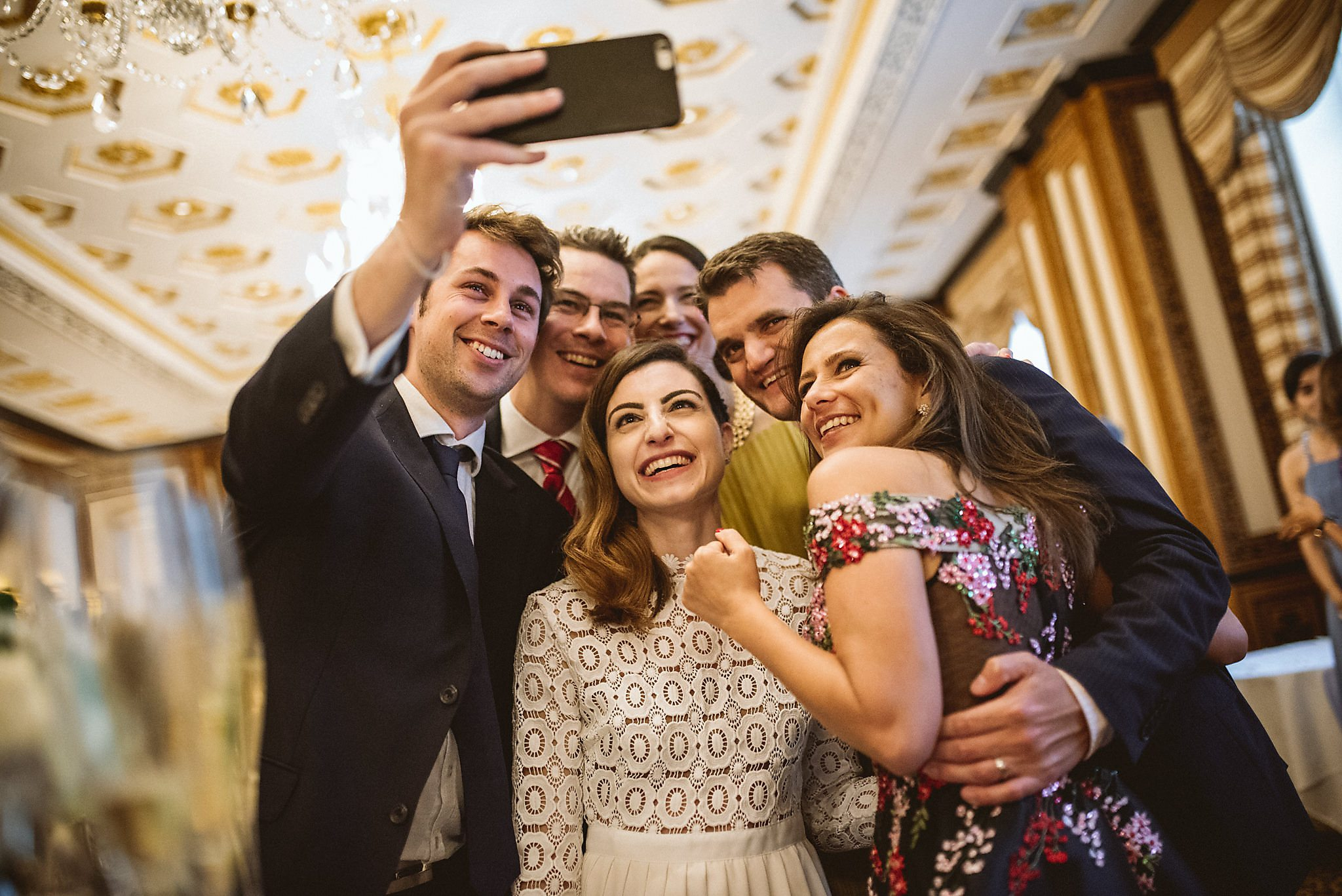 Bride Jo poses for a selfie with a group of guests at the Lanesborough Hotel