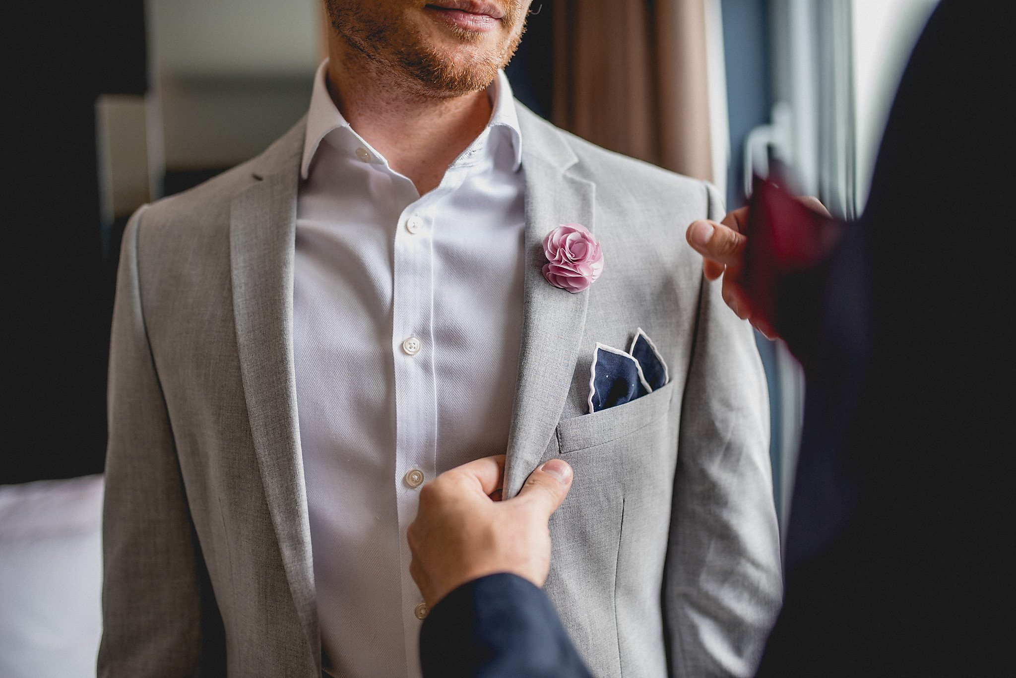 Straightening the lapel of the groom-to-be in pale grey suit and dark blue pocket square