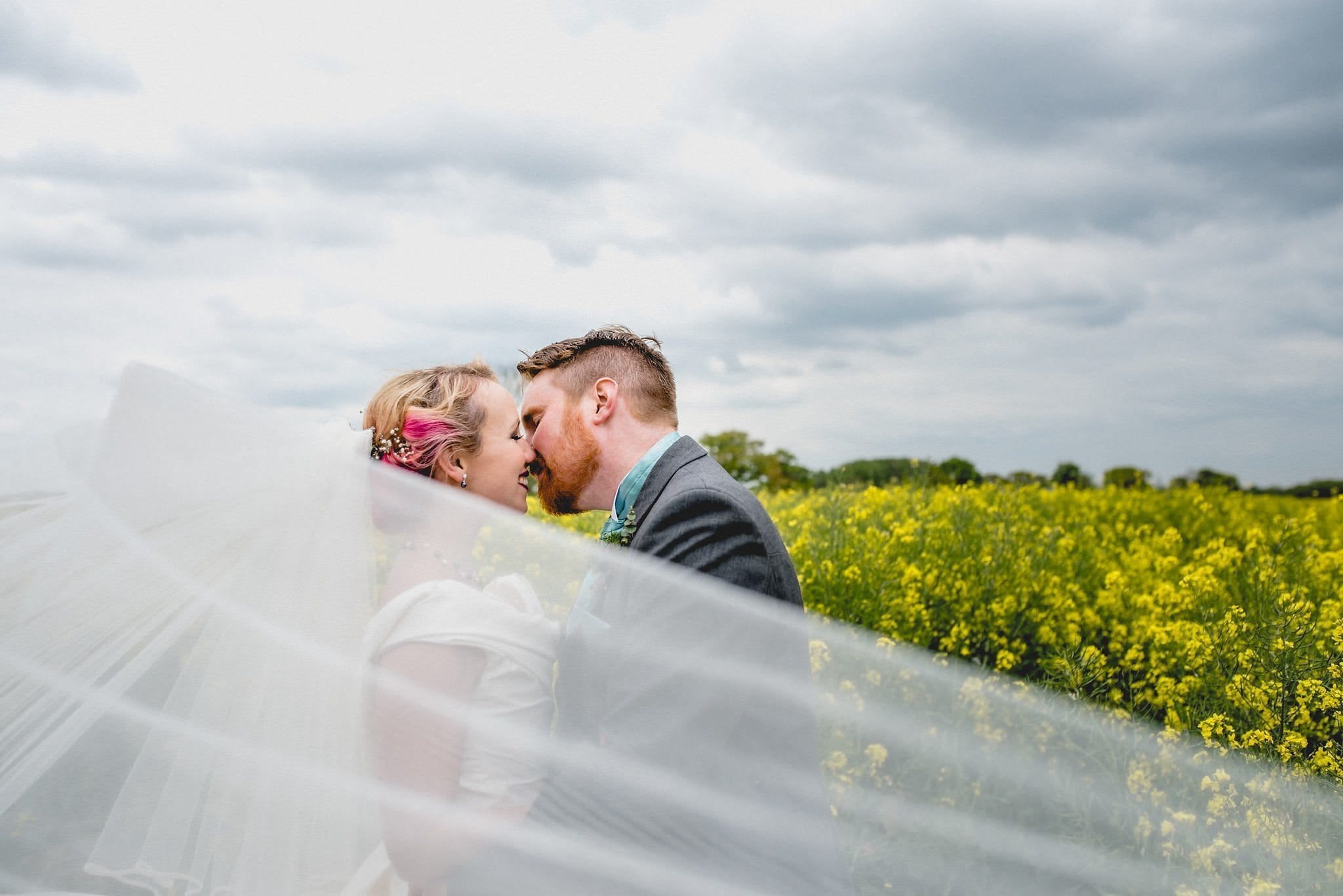 Hatty and Steven kiss, while her veil blows towards the camera. They stand in a field of bright yellow rape seed flowers while dark clouds gather above them