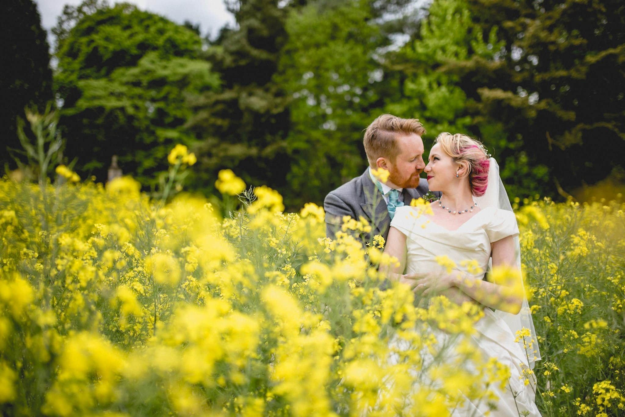 The newlyweds gaze into each others eyes surrounded by bright yellow rapeseed flowers