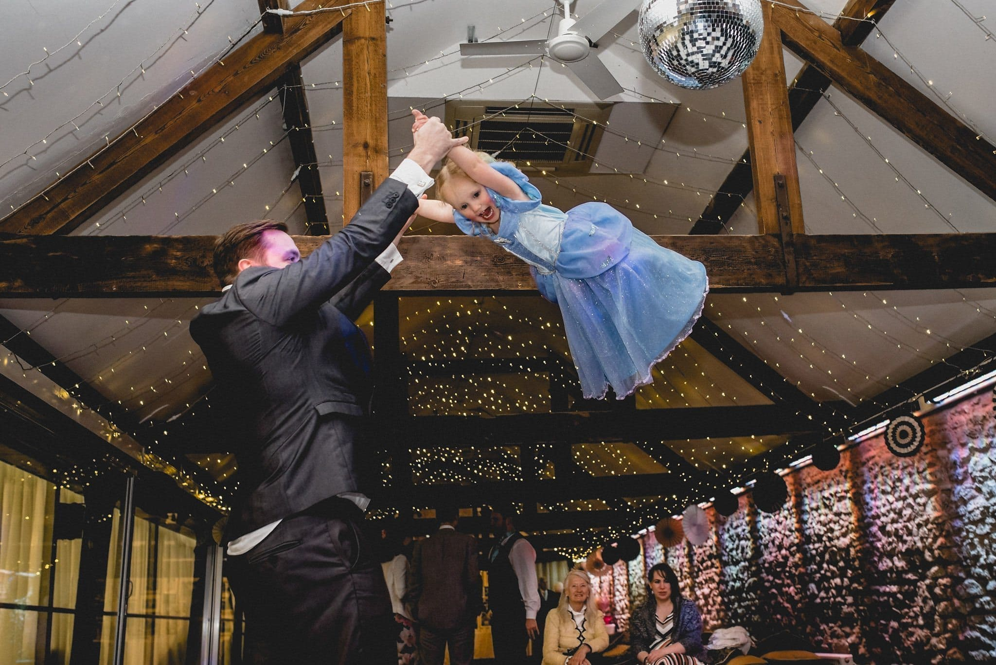 One of the children is swung high into the air on the dancefloor at Birtsmorton Court