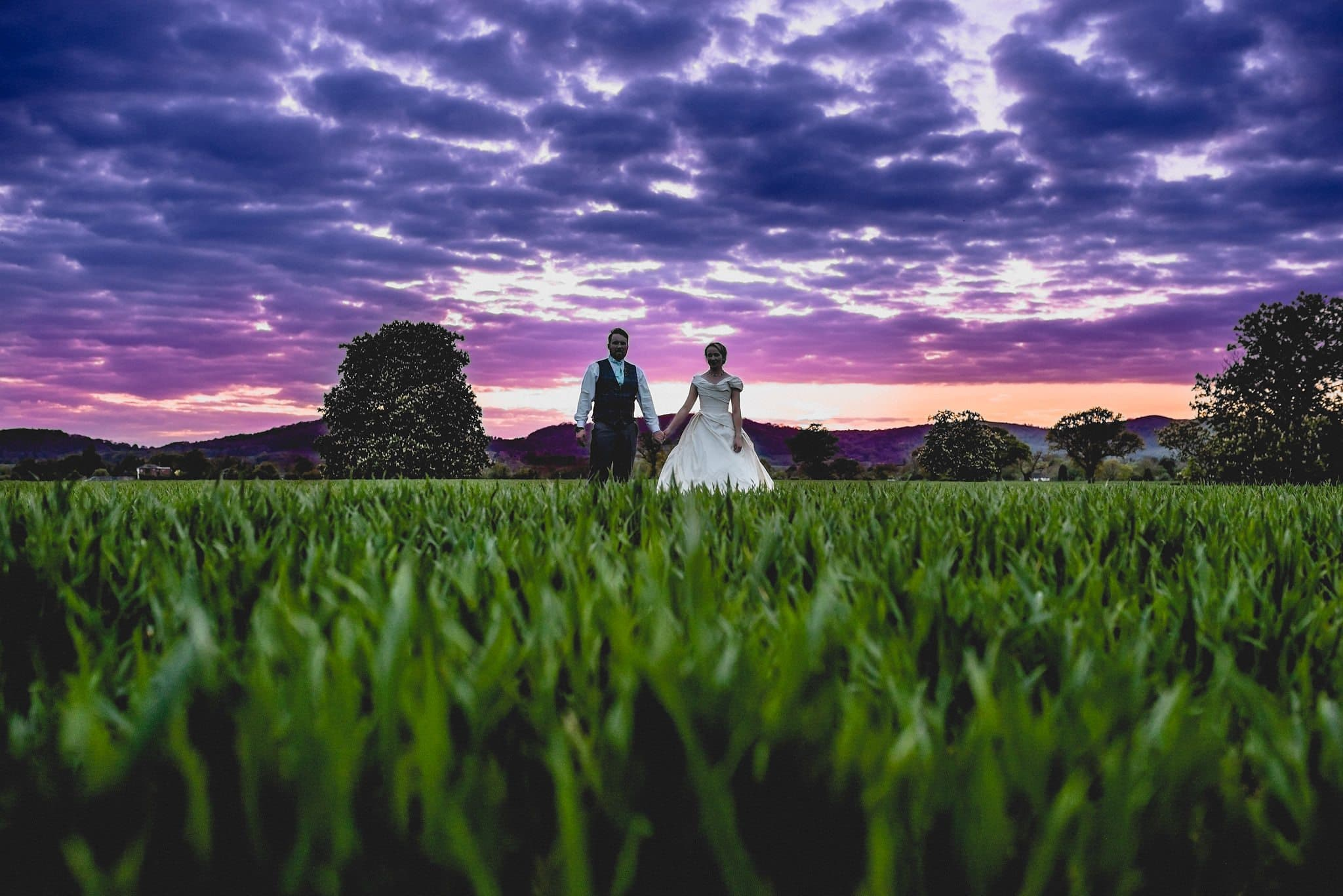 The couple stand in the long grass, hand in hand at sunset. The clouds look really dramatic in shades of mauve, pink and purple