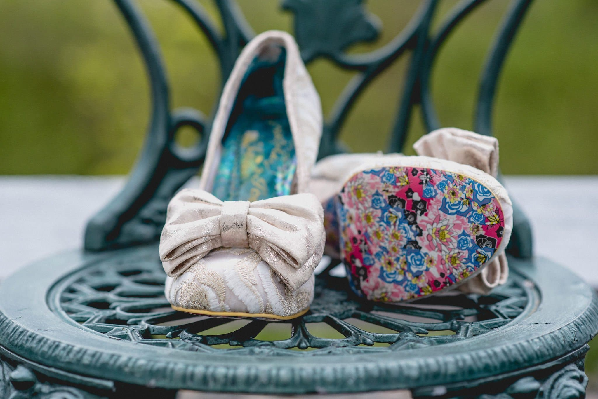 Velvet Irregular Choice shoes with a bow and painted floral soles are pictured on a metal filigree chair