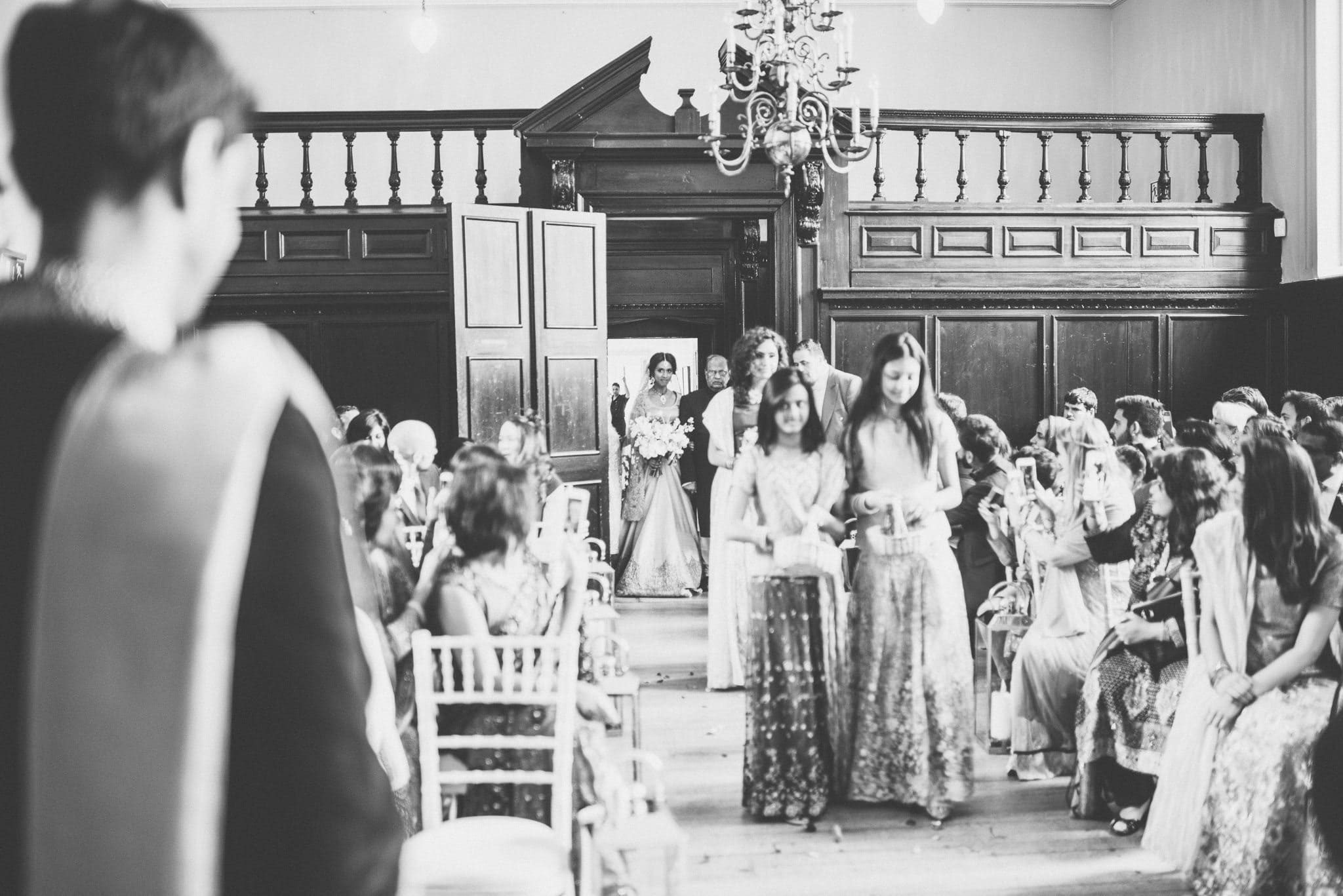 A black and white shot of Sorayya making her entrance and walking down the aisle at Fulham Palace