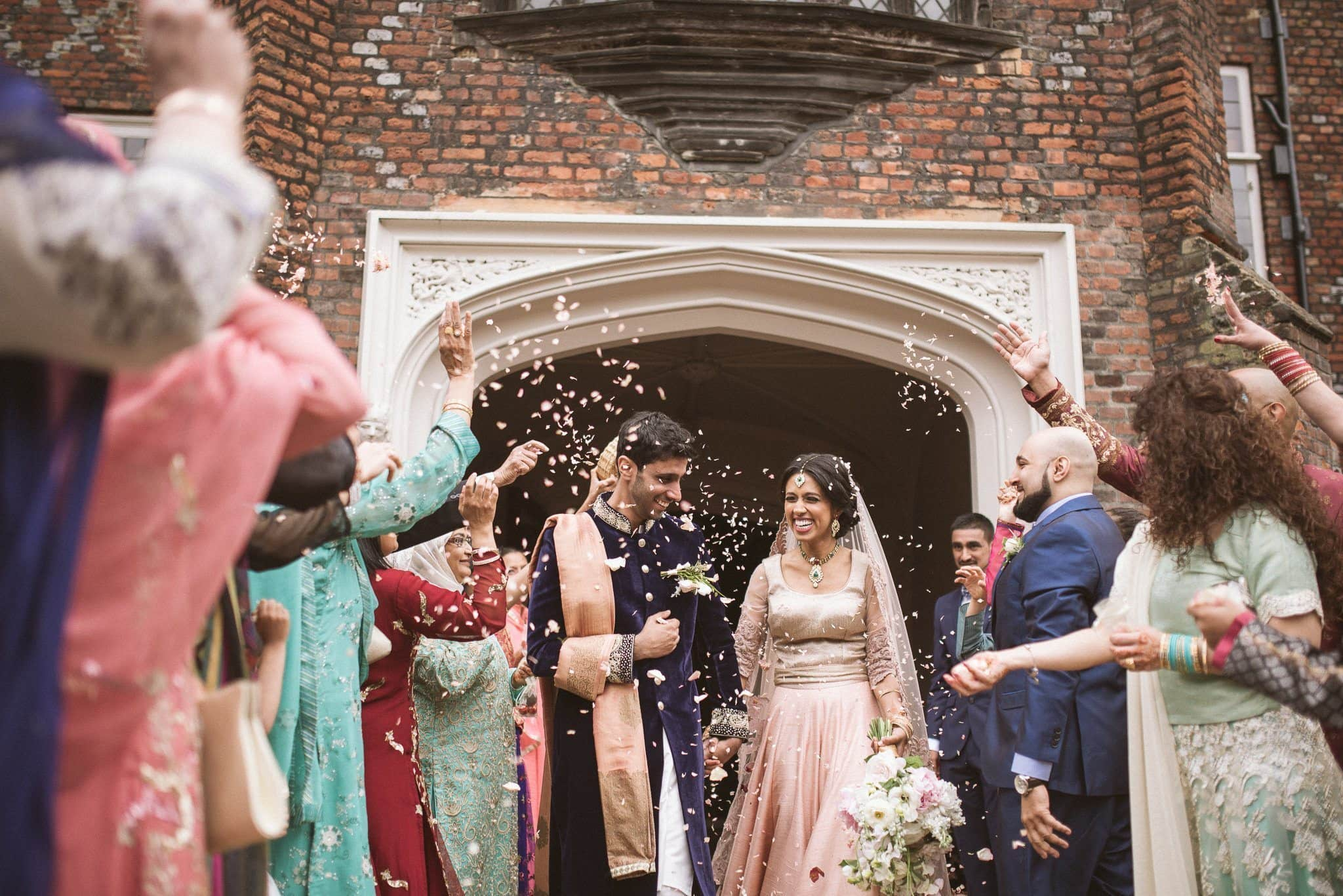 The couple emerge into the courtyard under a shower of rose petal confetti