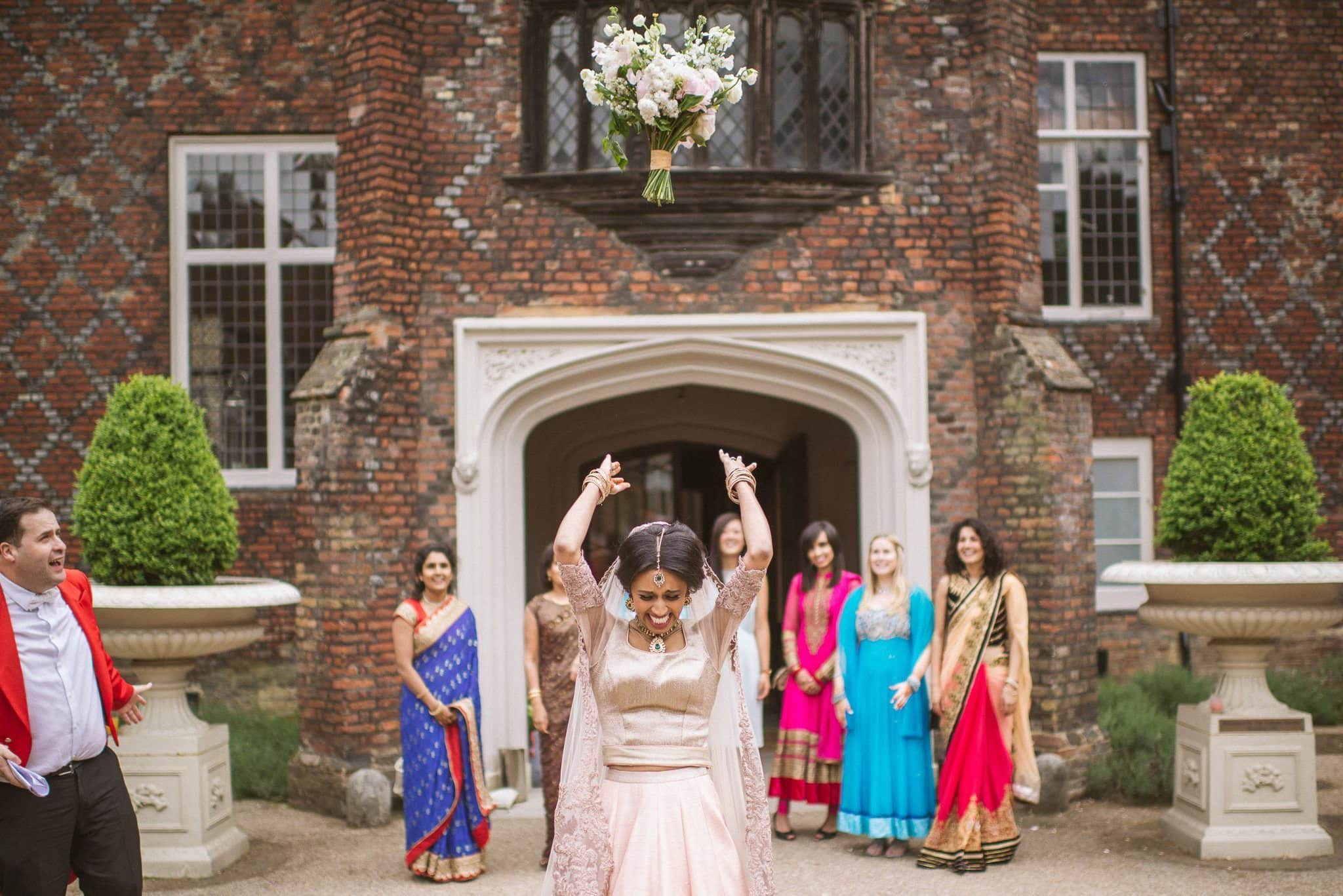 Sorayya throws her bouquet backwards over her head and the guests behind her run to catch it