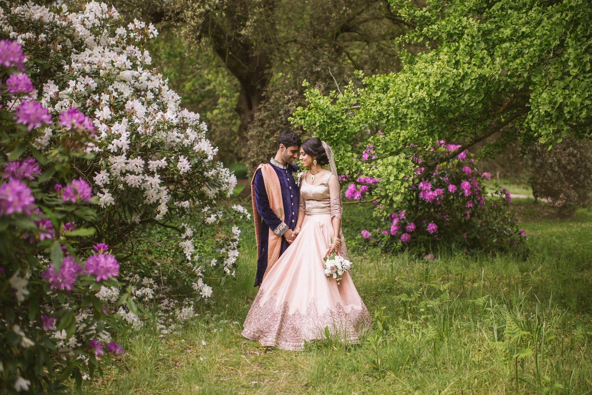 Sorayya and Usman gaze at each other surrounded by white and purple flowers in the grounds of Fulham Palace