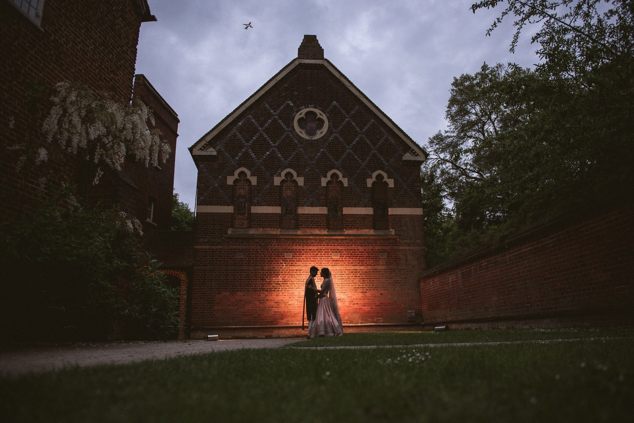 A silhouette of Sorayya and Usman against the chapel at Fulham Palace at twilight