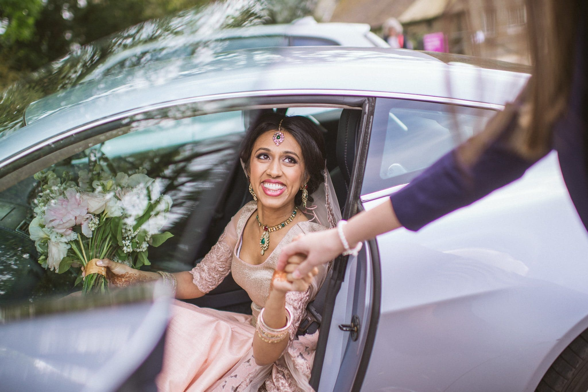 Sorayya takes a friend's hand as she exits the car at her Colourful Muslim Fulham Palace Wedding