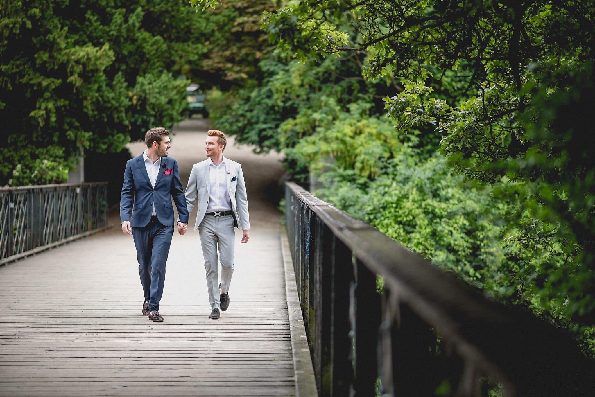 Drew and Tom walk hand in hand across the bridge in Ørstedsparken, Copenhagen