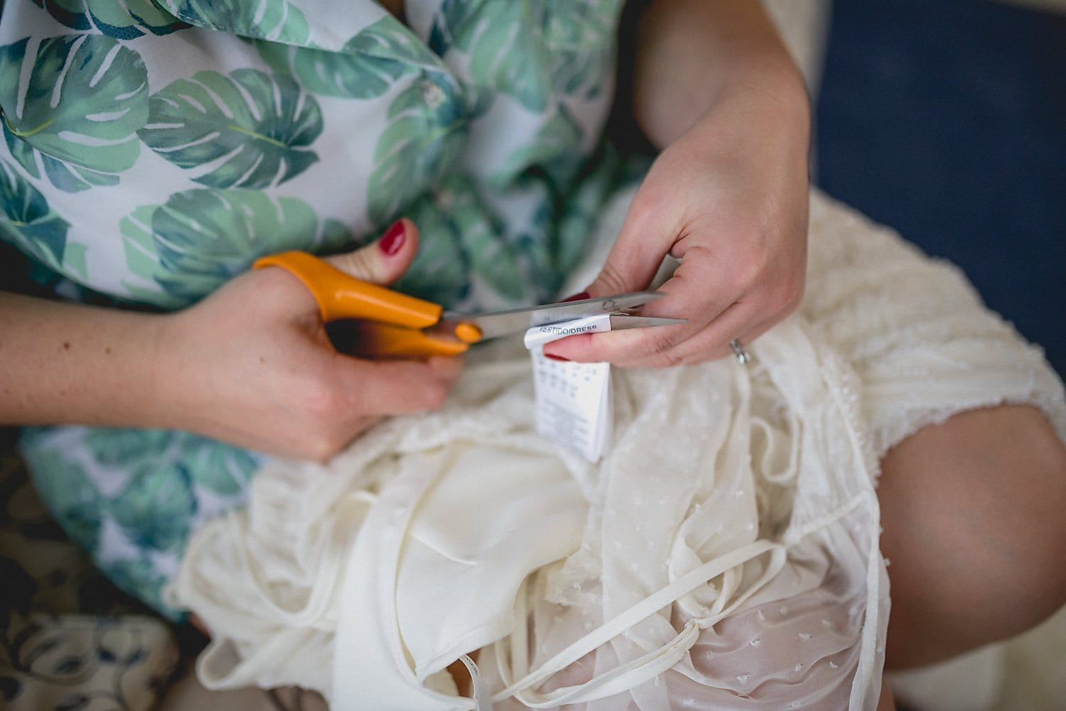 Bride cutting label of her wedding dress