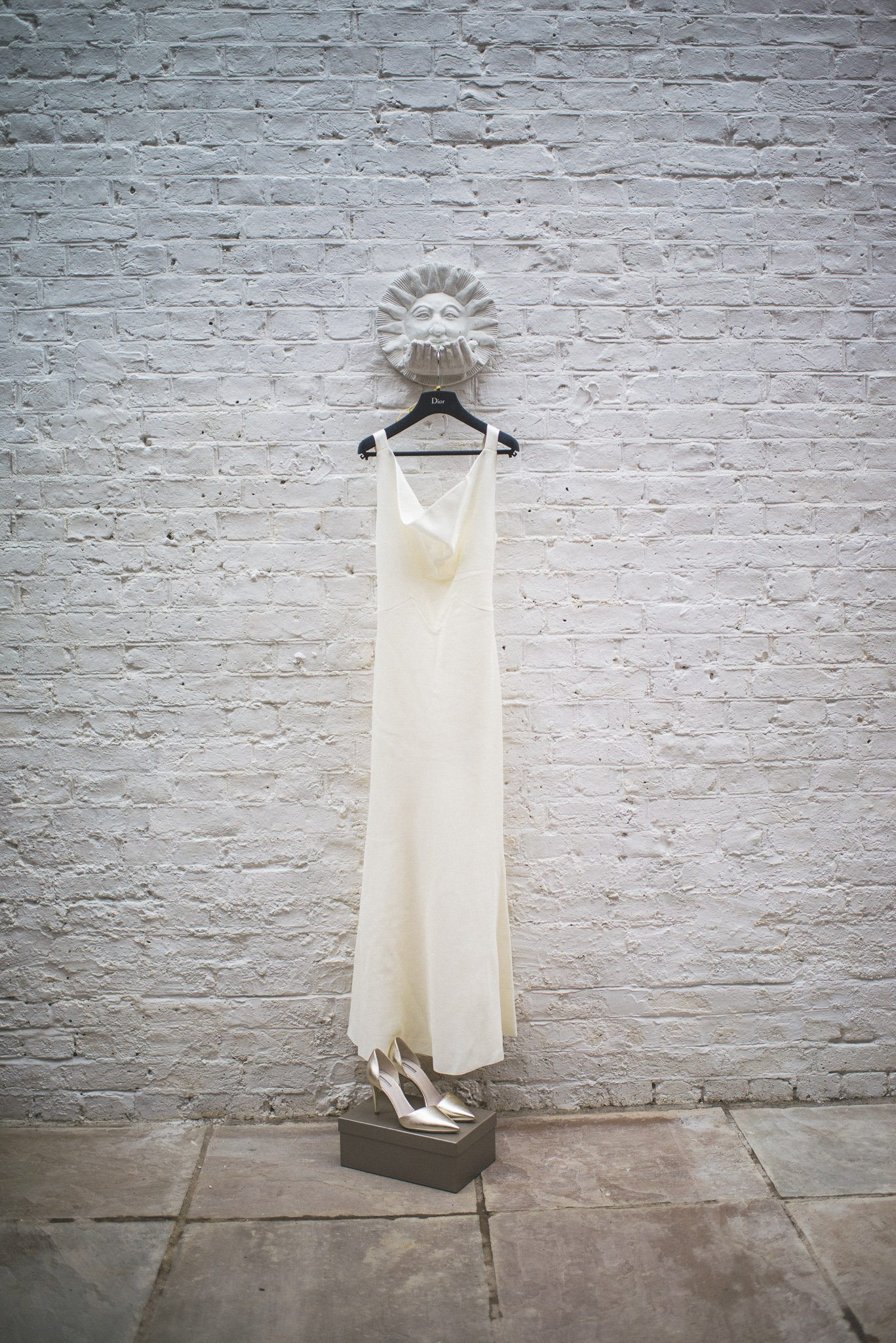 Ilaria's Dior gown and gold Armani shoes hang in front of a white brick wall