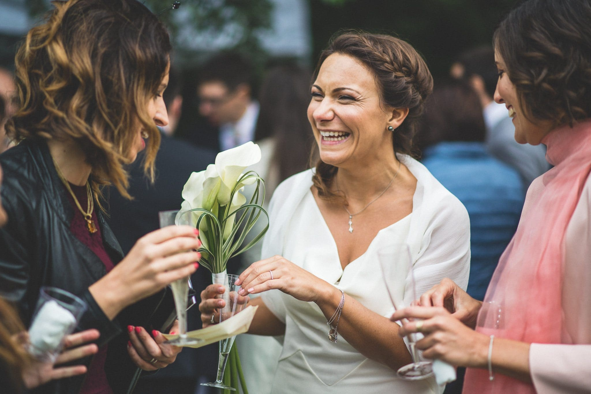 Ilaria laughs with female guests after her wedding ceremony, while holding her bouquet of calla lilies
