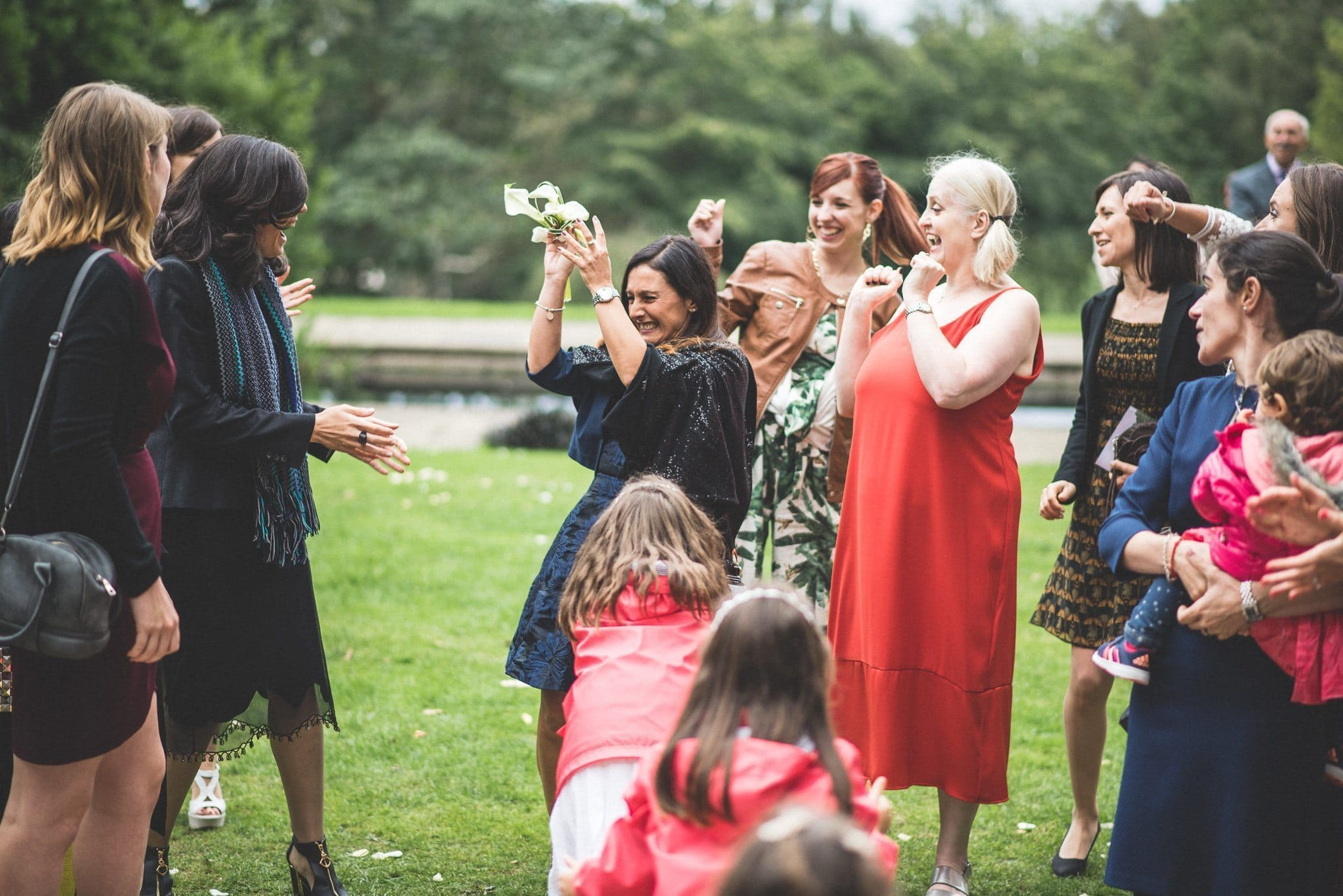 The bouquet is caught by a guest in a black dress while others applaud and cheer