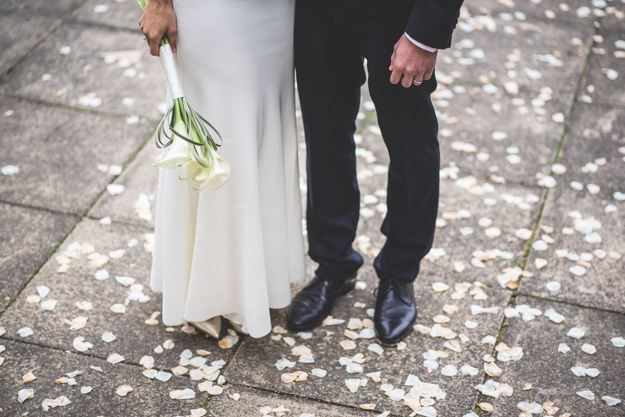 A three-quarter length shot of Marco and Ilaria from the waist down, standing amid the petal confetti after their wedding ceremony